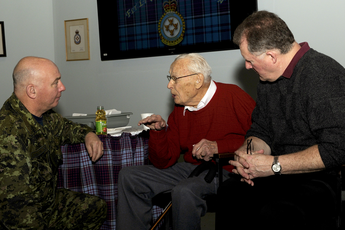 During his 98th birthday celebration at 16 Wing Borden, Ontario, Flight Lieutenant (retired) Glen Rawson chats with Master Warrant Officer Andy Galton (left) and Master Warrant Officer (retired) Normand Marion (right). PHOTO: DND, BM2015-2000-12