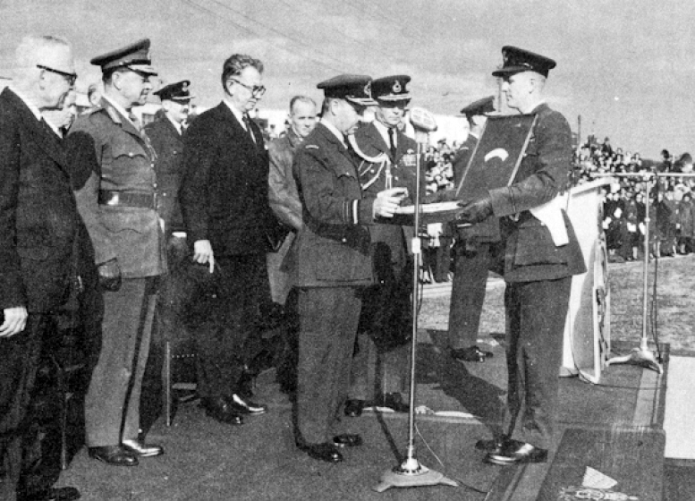 "Air Marshal Wilfred Curtis prepares to present a silver plaque to the Marshal of the Royal Air Force, the Lord Tedder, Chief of the Air Staff, Royal Air Force, during the presentation of the BCATP Memorial Gates on September 30, 1949, at RCAF Station Trenton, Ontario. The plaques were presented to representatives of the British, Australian, New Zealand and American air forces as ""a tangible memento of our continuing friendship"". PHOTO: From the presentation ceremony commemorative booklet"