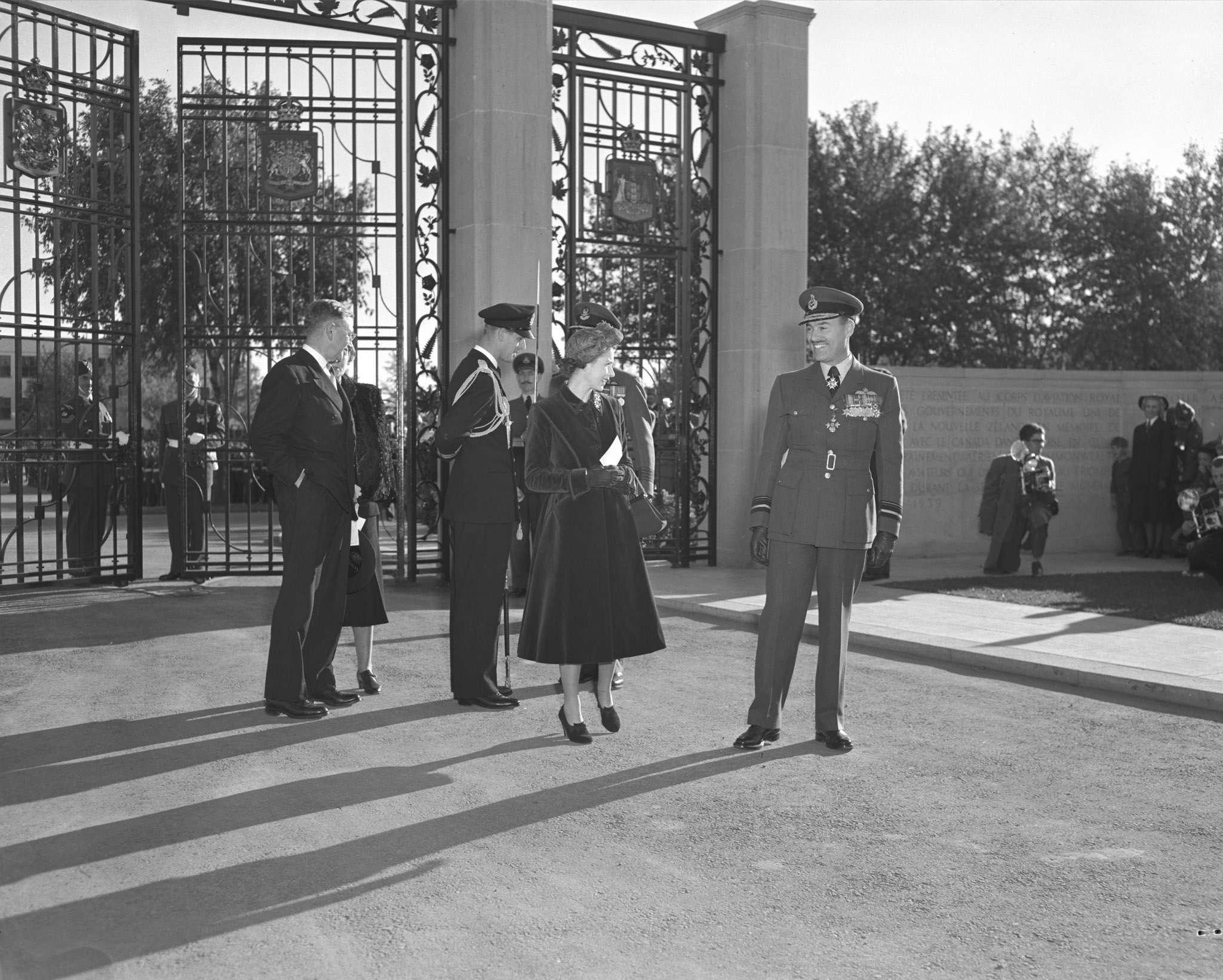 Air Vice Marshal Charles Roy Slemon, the air officer commanding of Training Command, speaks with Princess Elizabeth on the Royal Couple's arrival at Trenton. The Duke of Edinburgh is with parade commander, Group Captain G.P. Dunlop (partly obscured), while Defence Minister Brooke Claxton and his wife, Helen Claxton, look on. PHOTO: DND Archives, PL-52814