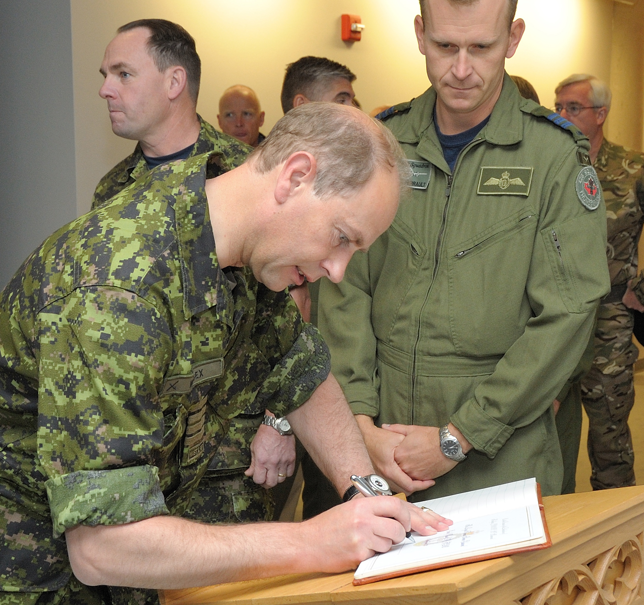 His Royal Highness Prince Edward signs a guest book before unveiling a memorial honouring crew members of a Halifax bomber that was shot down over Belgium in 1944. PHOTO: Corporal Levarre McDonald, TN2012-0422-01