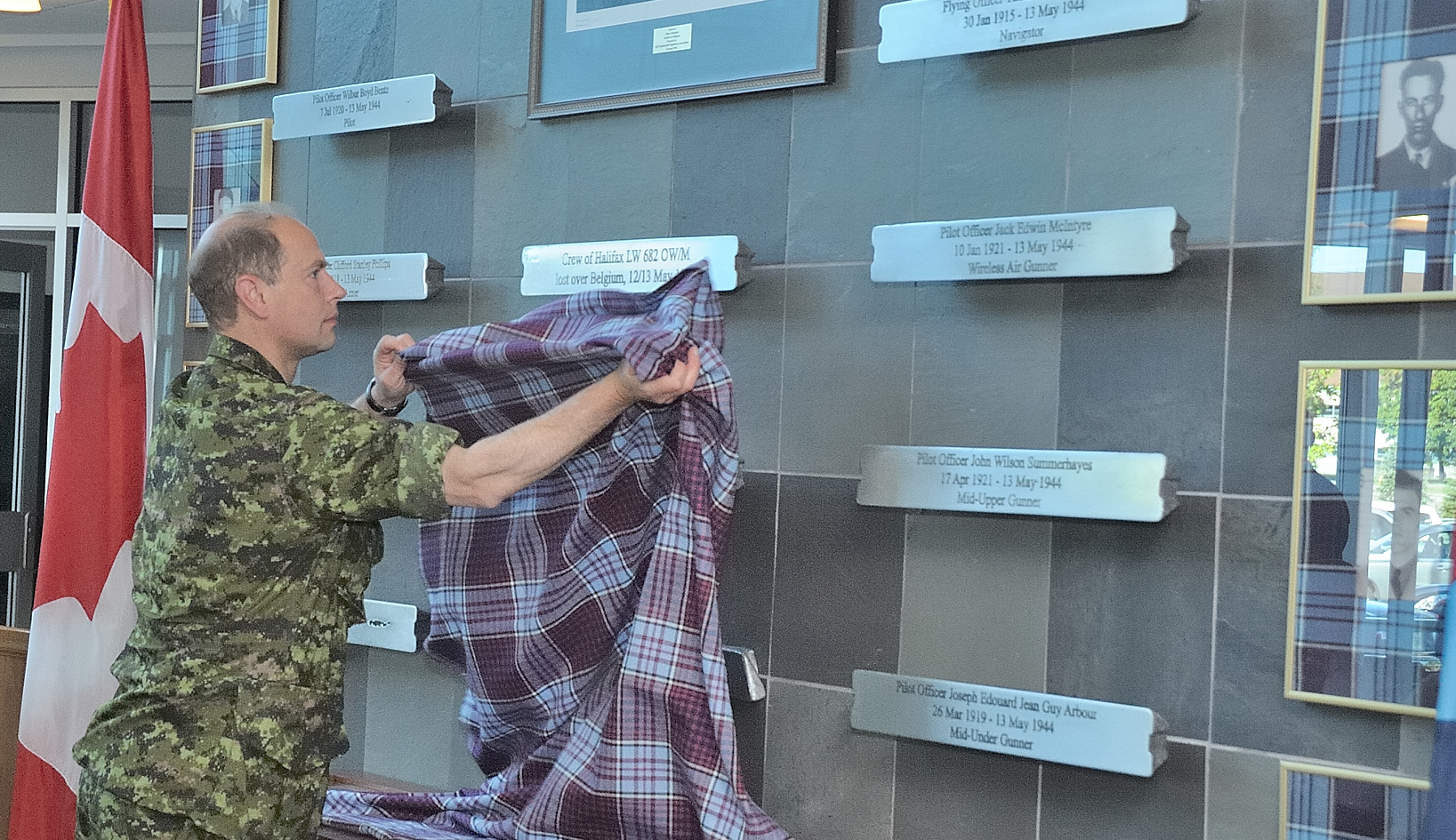 A man in a green disruptive pattern uniform lifts a blue tartan cloth off a wall that has engraved rectangles of metal affixed to it.