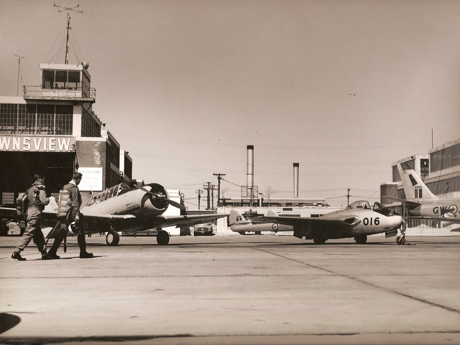 "In an undated photograph, 400 ""City of Toronto"" Squadron pilots head past a Harvard II toward a Vampire III aircraft at RCAF Station Downsview, Ontario. PHOTO: Via History Hangar website"
