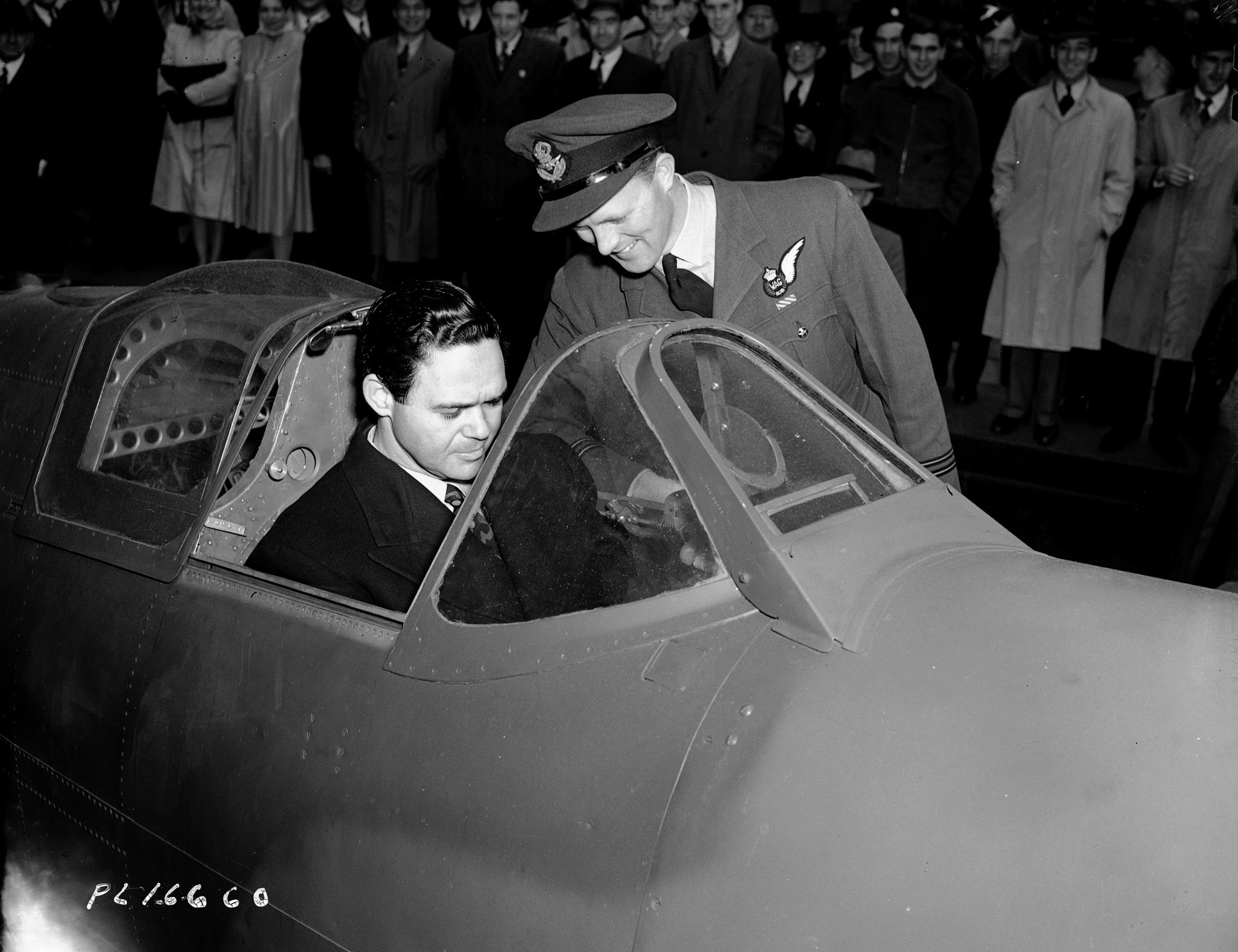 Flight Lieutenant George A. Casey, who received the Distinguished Flying Cross for his work at Dieppe, shows the New York City Metropolitan Opera's James Melton around the cockpit of a Spitfire fighter aircraft outside City Hall at the start of Air Force Week in Toronto on May 10, 1943. The two had just addressed a huge crowd gathered at City Hall for the first day of Air Force Week and the last day of the fourth Victory Loan Drive. PHOTO: DND Archives, PL-16660