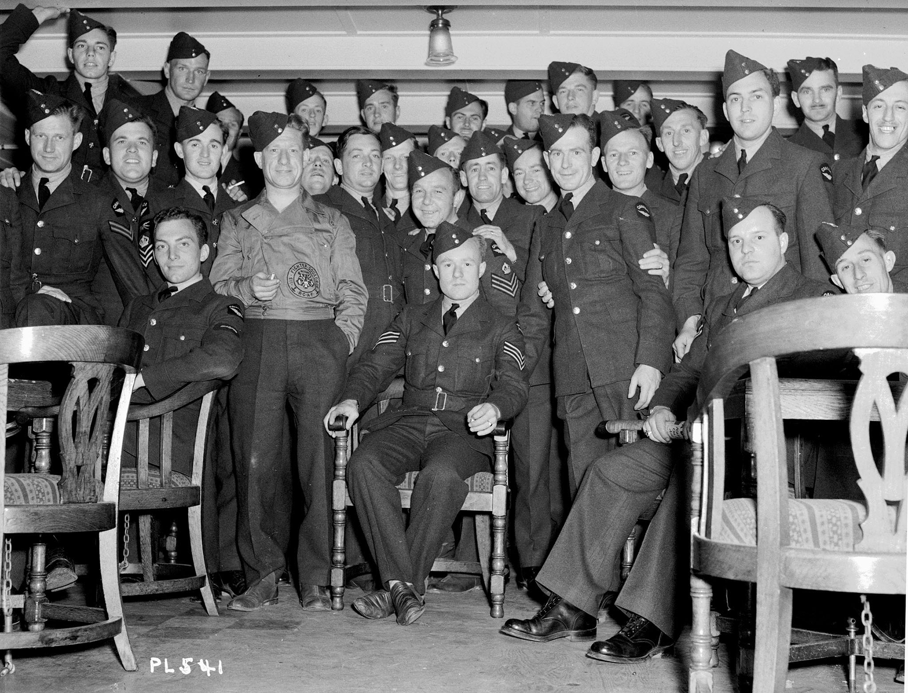 Thirty uniformed men gather for a photograph in a low-ceilinged room.