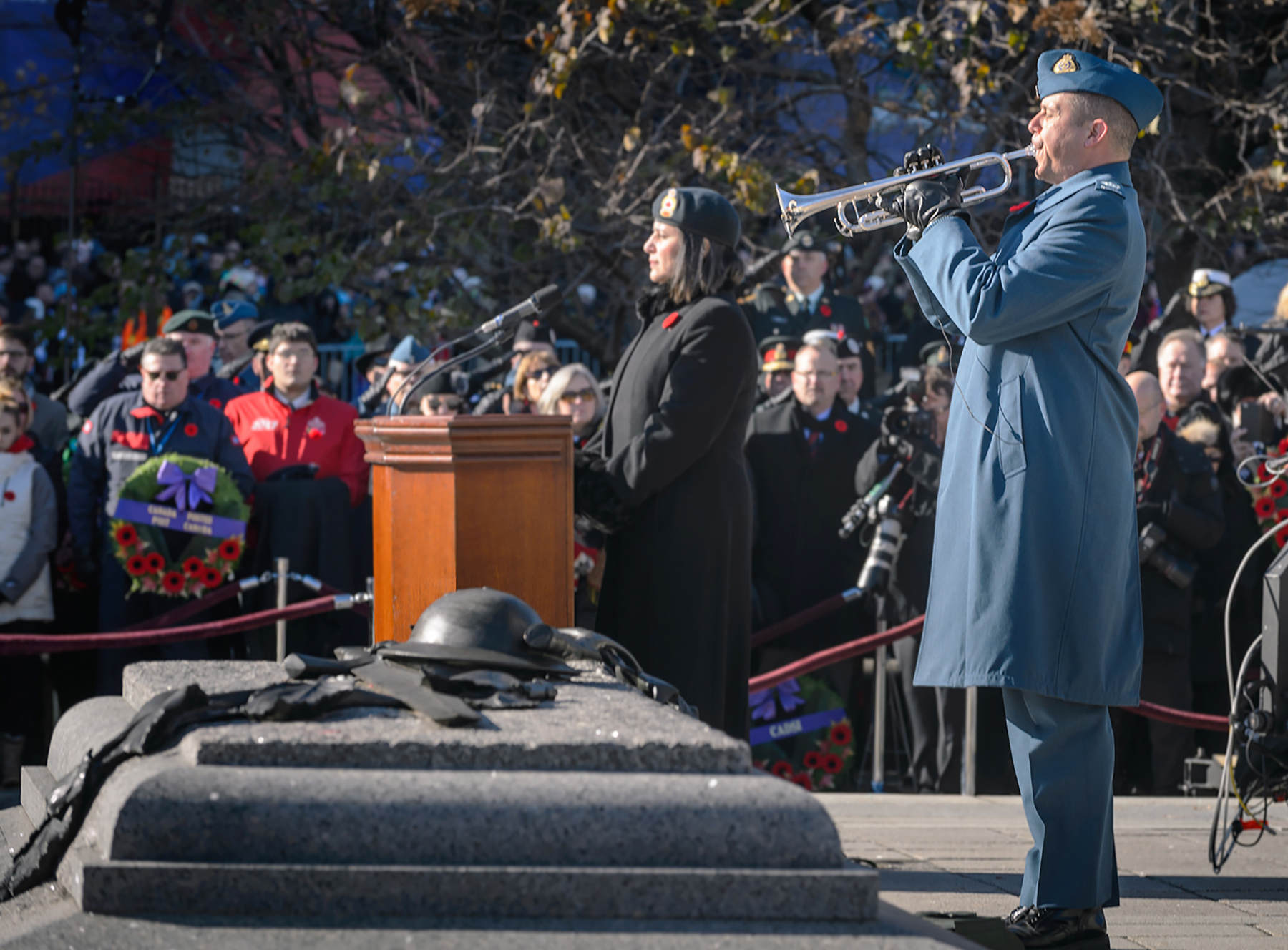 A man in a blue uniform plays a trumpet by a stone tomb with a metal soldier's helmet; a woman in a black uniform stands at a podium. Both wear poppies. Behind them are military members and civilians.