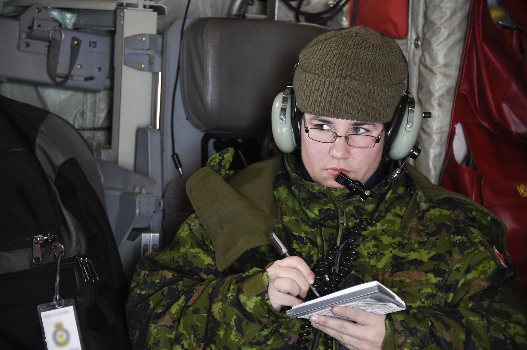 A woman wearing a disruptive pattern uniform, a tuque and noise-cancelling headphones sits in a cargo aircraft taking notes.