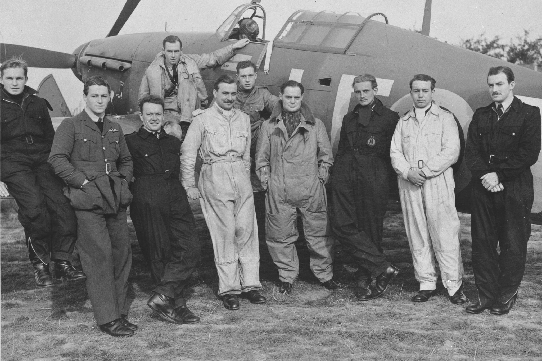 A group of men in various uniforms stand in front of a single propeller aircraft.