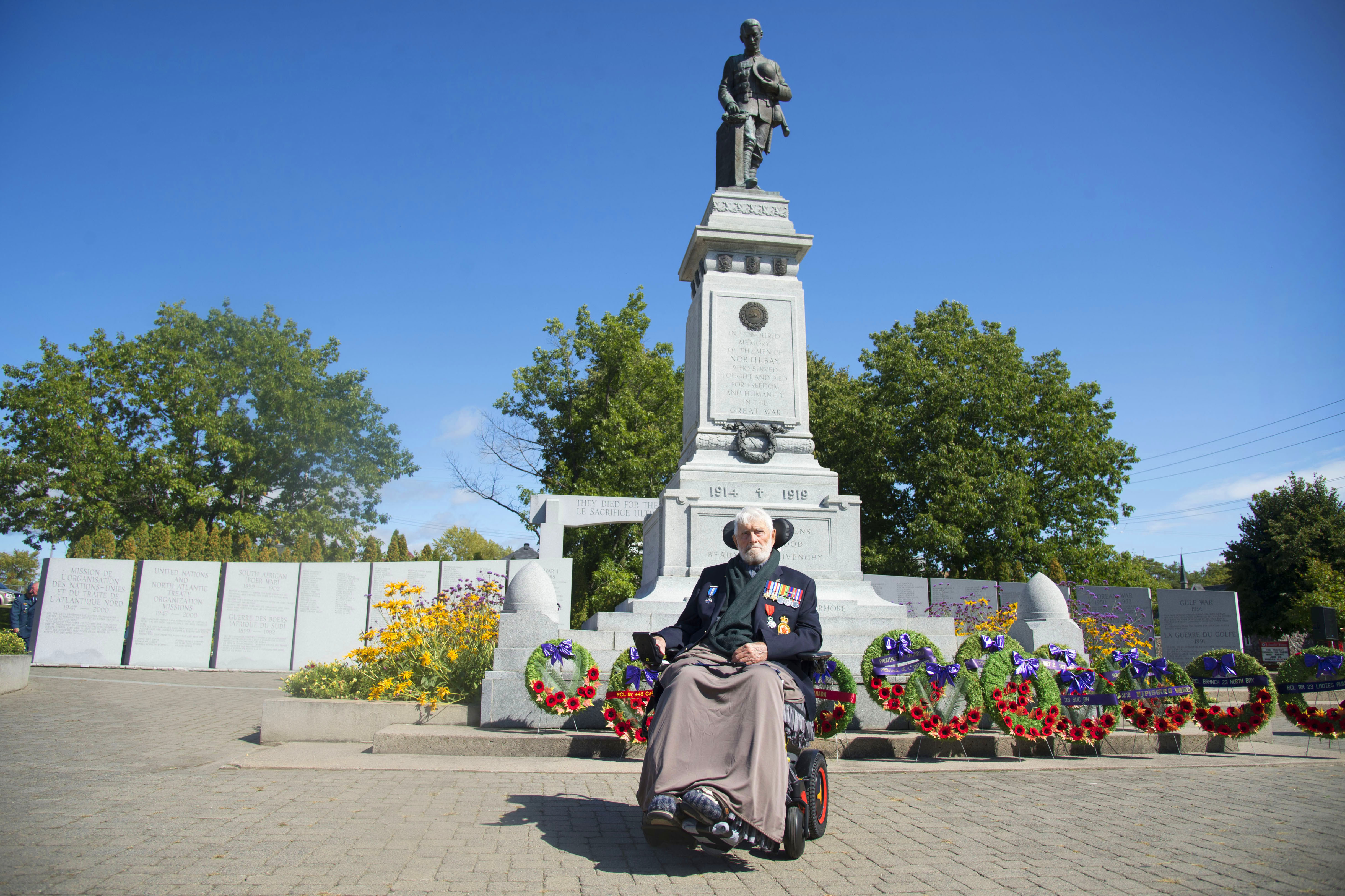 An elderly man wearing a dark jacket displaying many medals sits in a wheelchair in front of a large monument topped by a bronze soldier and fronted by wreaths on stands.