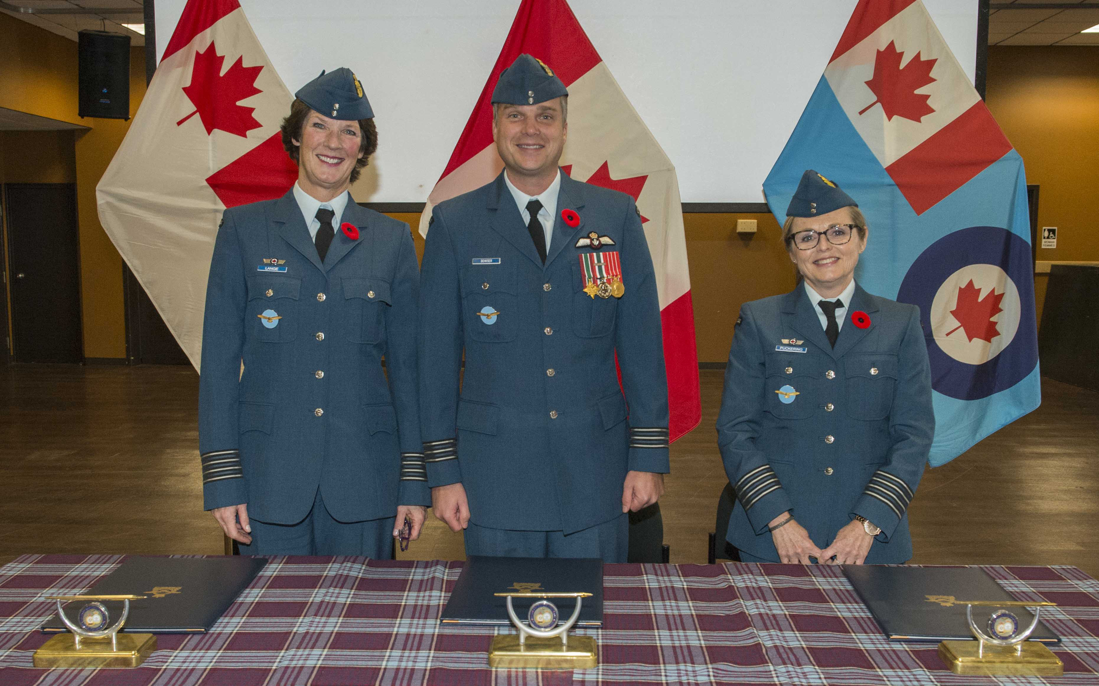 436 Squadron's outgoing honorary colonel, Julie Lange (left), 436 Squadron commanding officer Lieutenant-Colonel Andy Bowser, and the squadron's incoming honorary colonel, Cathie Puckering, are ready to sign the honorary colonel change of appointment documents during a ceremony at 8 Wing Trenton, Ontario on November 1, 2019. PHOTO: Corporal Rob Stanley, TN08-2019-0412-001