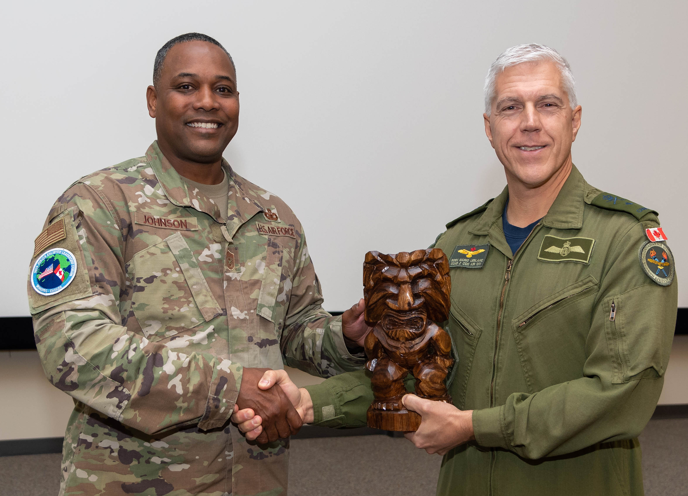 Chief Master Sergeant Anthony Johnson of the United States Air Force (left) presents a memento to Brigadier-General Mario Leblanc, commander of 2 Canadian Air Division, during the Junior Enlisted Leadership Forum held at 17 Wing Winnipeg, Manitoba, from October 21 to 25, 2019. PHOTO: Corporal Brian Lindgren, WG2019-0525-013
