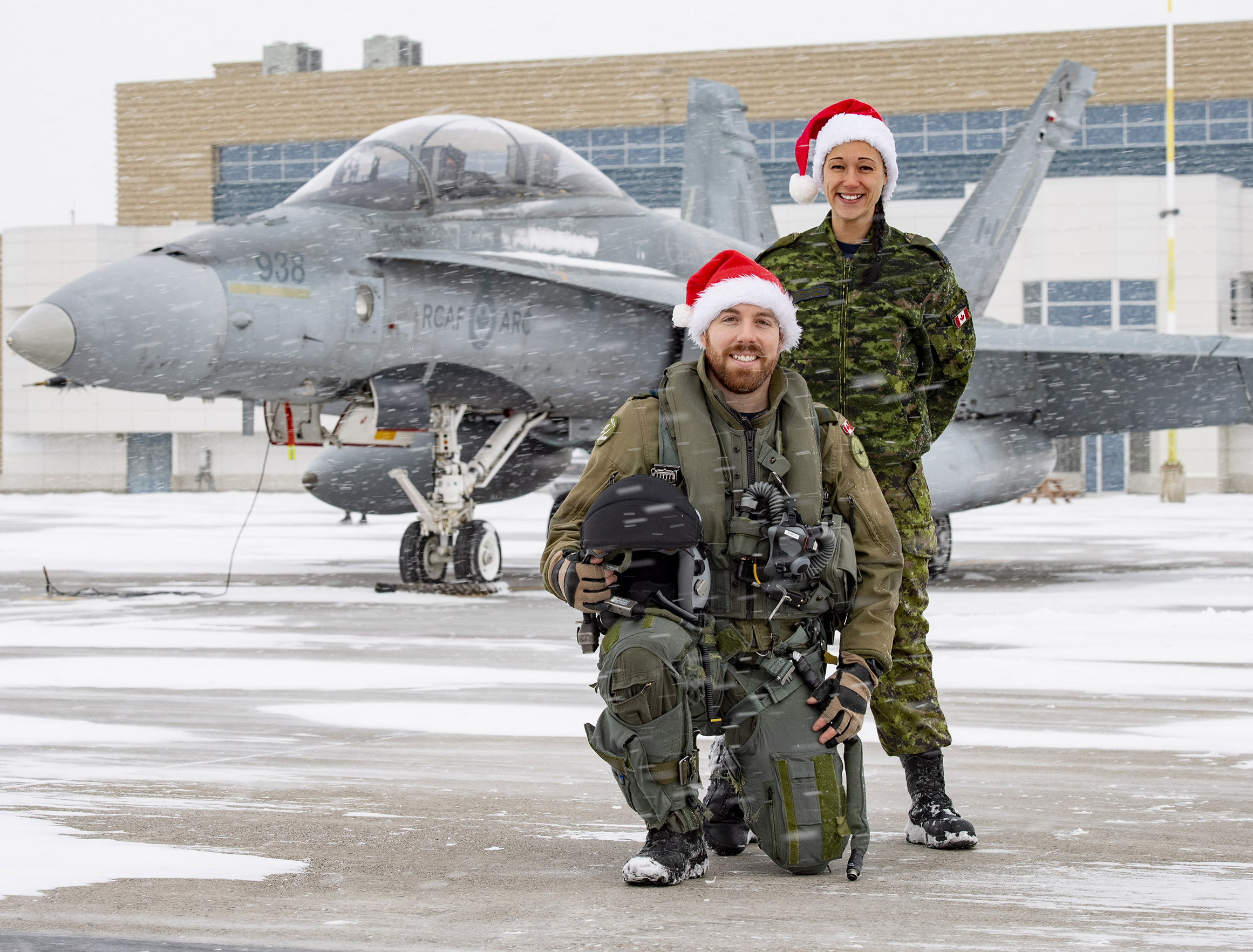 "Two people, one kneeling and one standing, are on a snowy tarmac with a fighter jet behind them. Both wear military uniforms and ""Santa"" hats."