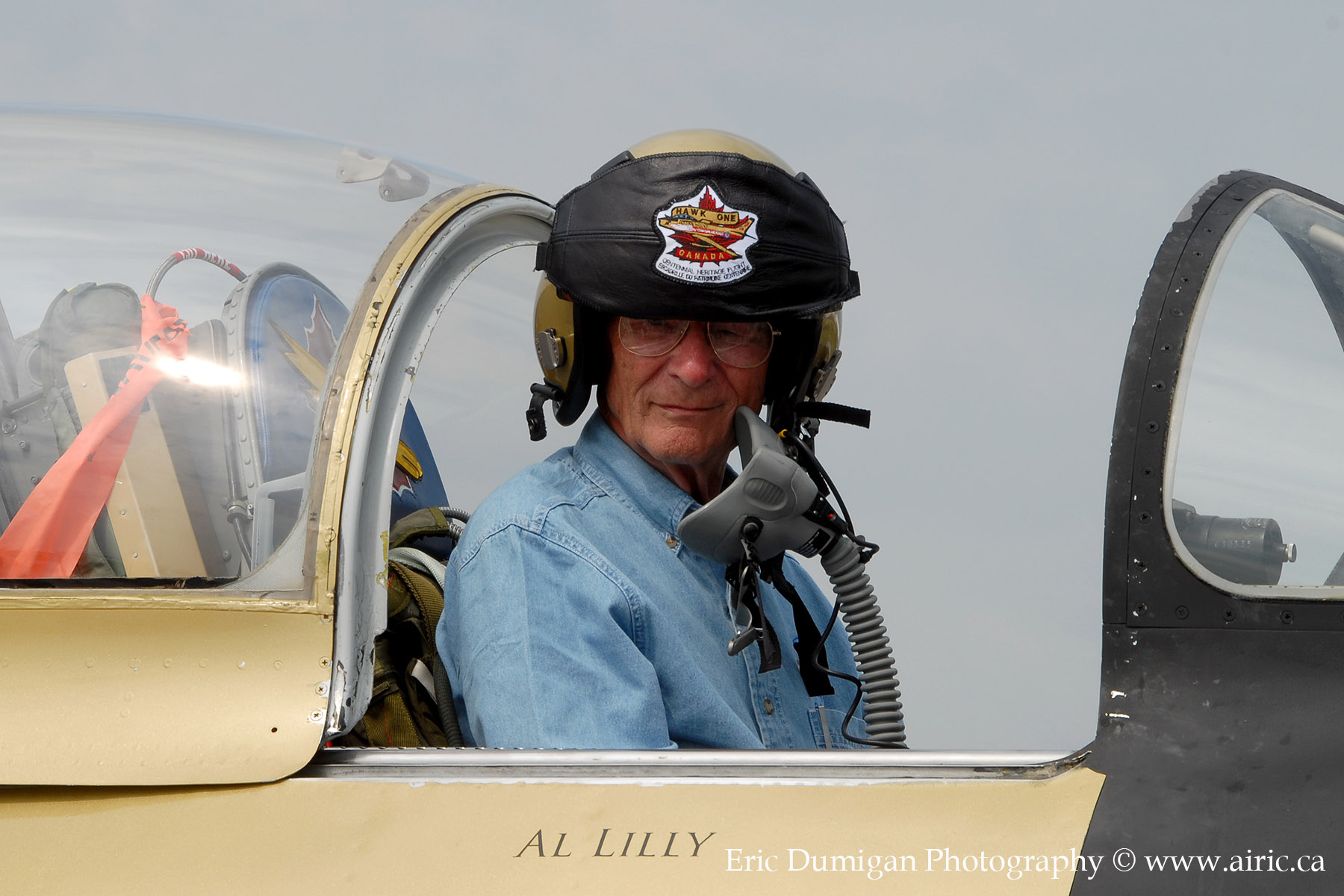 An older man, wearing a flying helmet, sits in the cockpit of a small aircraft that has its canopy open.