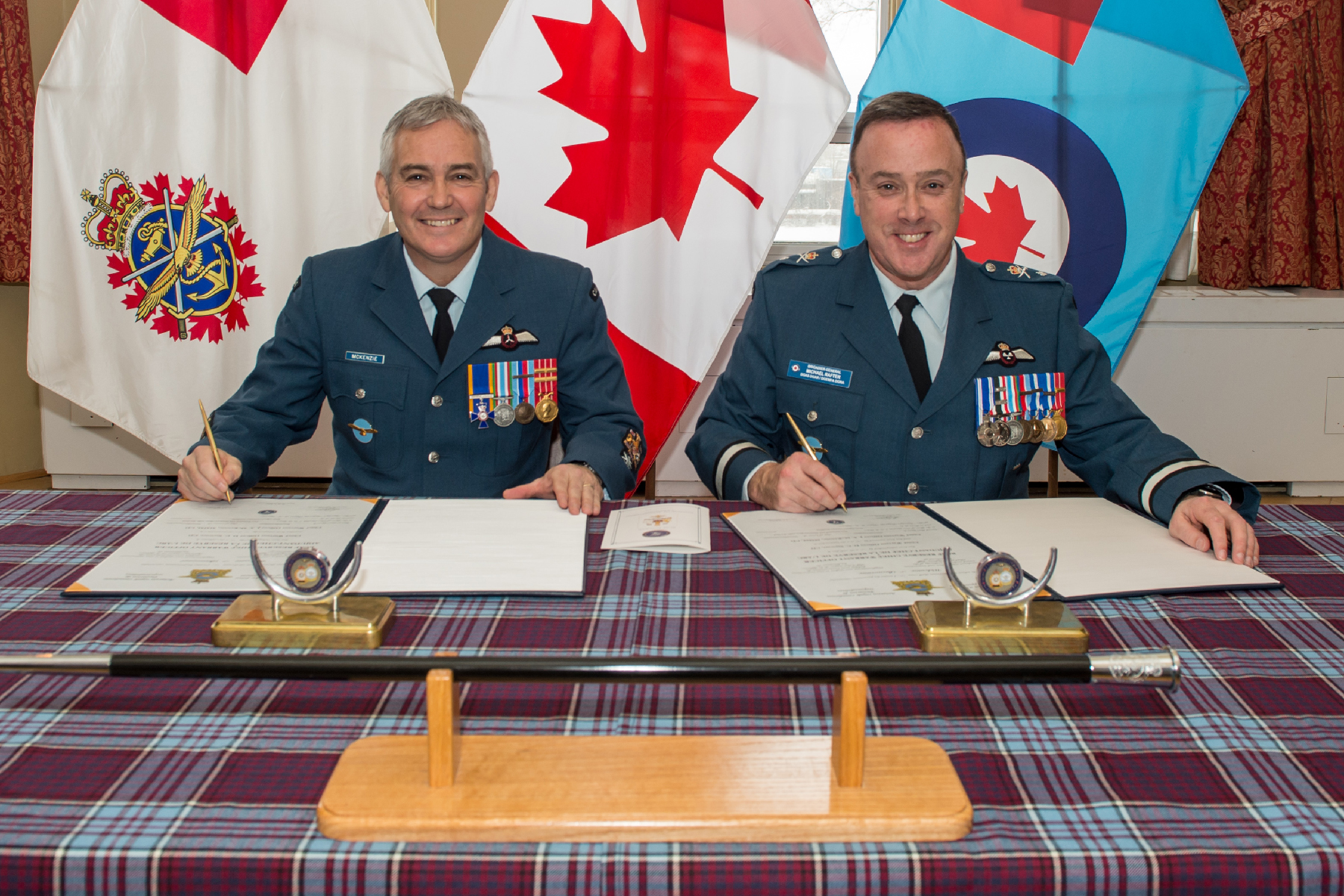 Two men in blue uniforms with medals sit facing the camera, side by side, at a table draped with tartan and backed by three flags. On the table in front of the men are documents and pens.