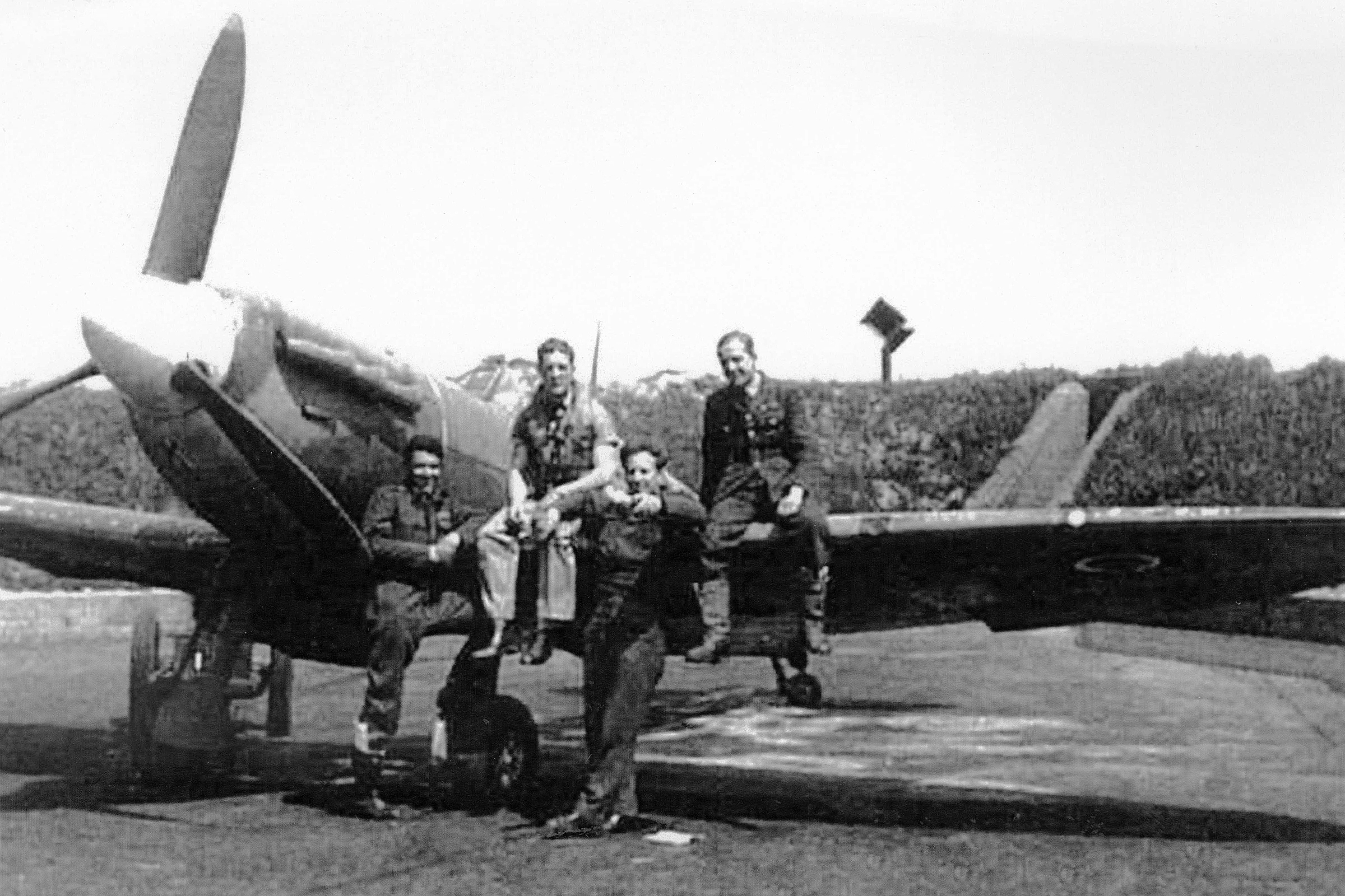 In a black-and-white photograph, two young men in uniform sit on the leading edge of the wing of a vintage propeller aircraft, and two more stand in front of the wing.