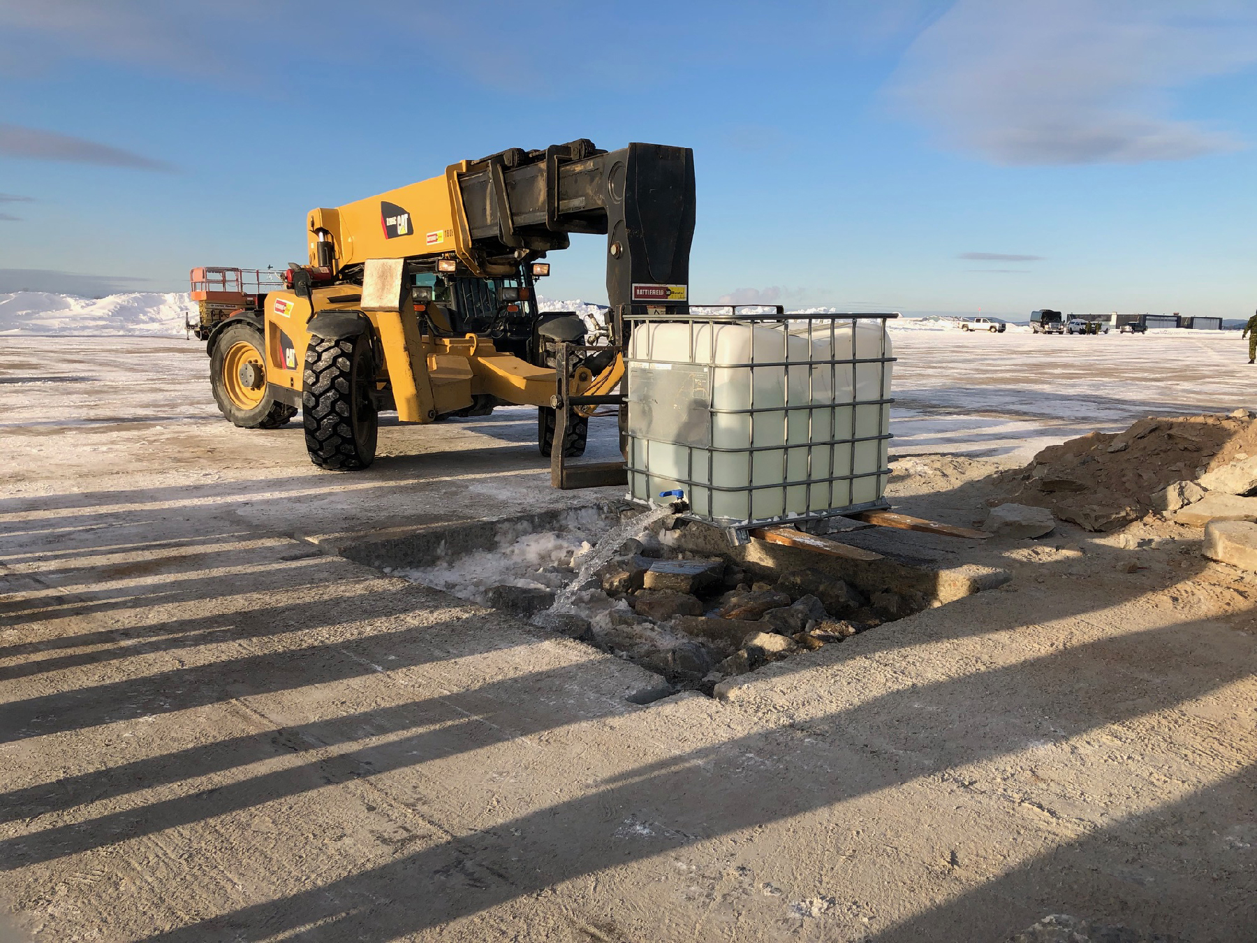 In winter, a large yellow construction-type vehicle pours water into a shallow, rectangular hole filled with stone debris.