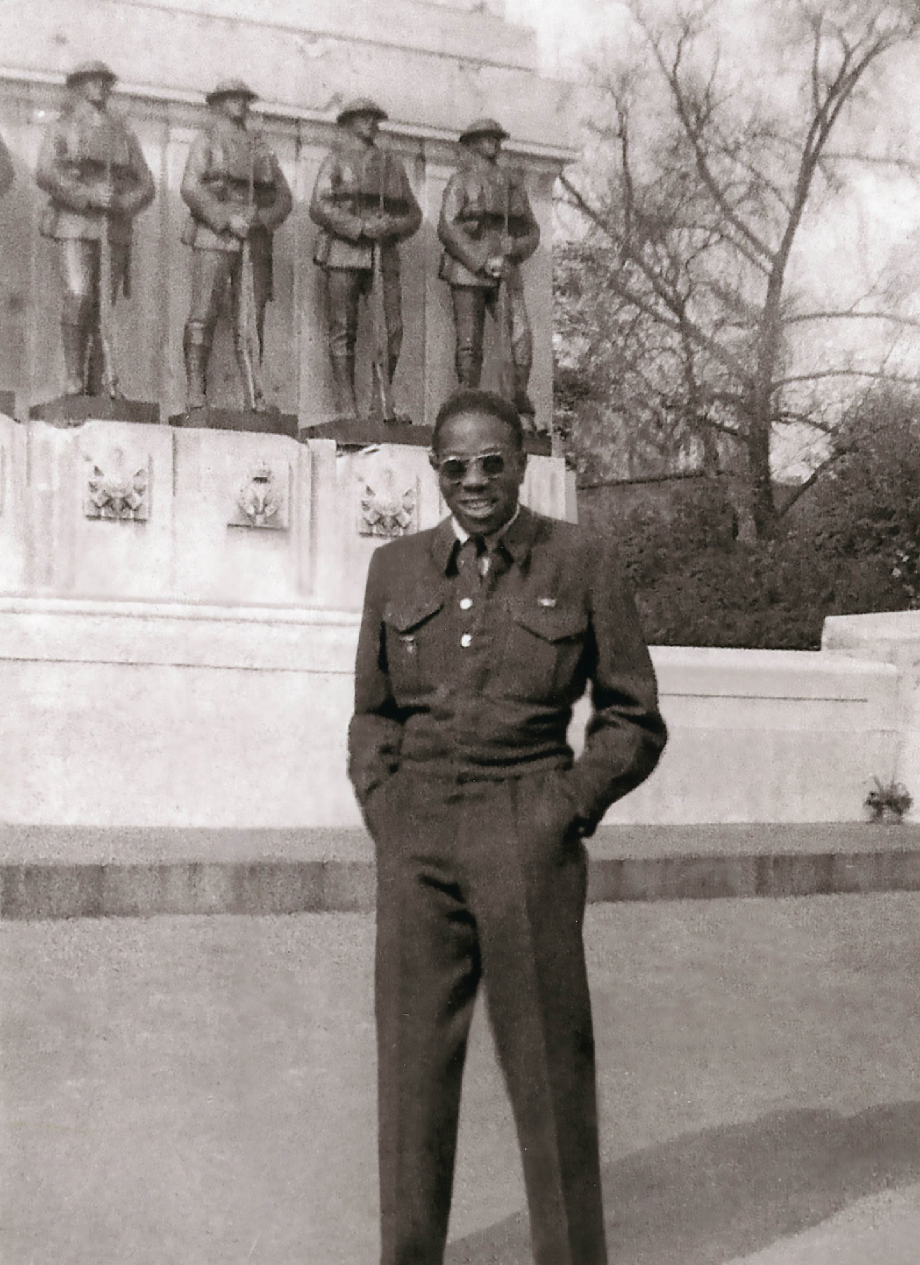 In a black-and-white photograph, a Black man wearing a uniform stands with his hands in his pockets in front of a large memorial displaying statues of men in uniforms.