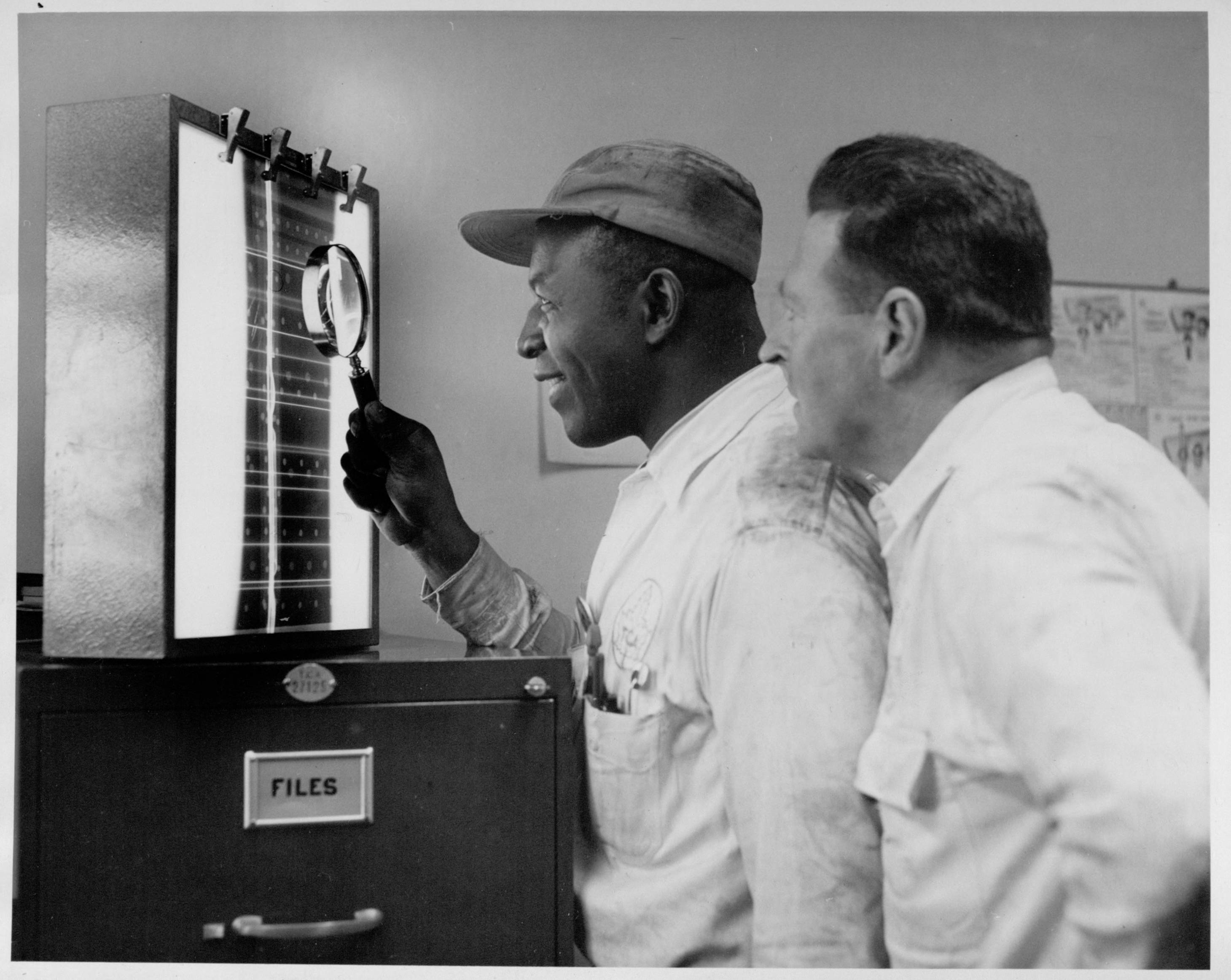A black and white photo of two men looking at an X-ray film mounted on a viewer, set on top of a file cabinet.