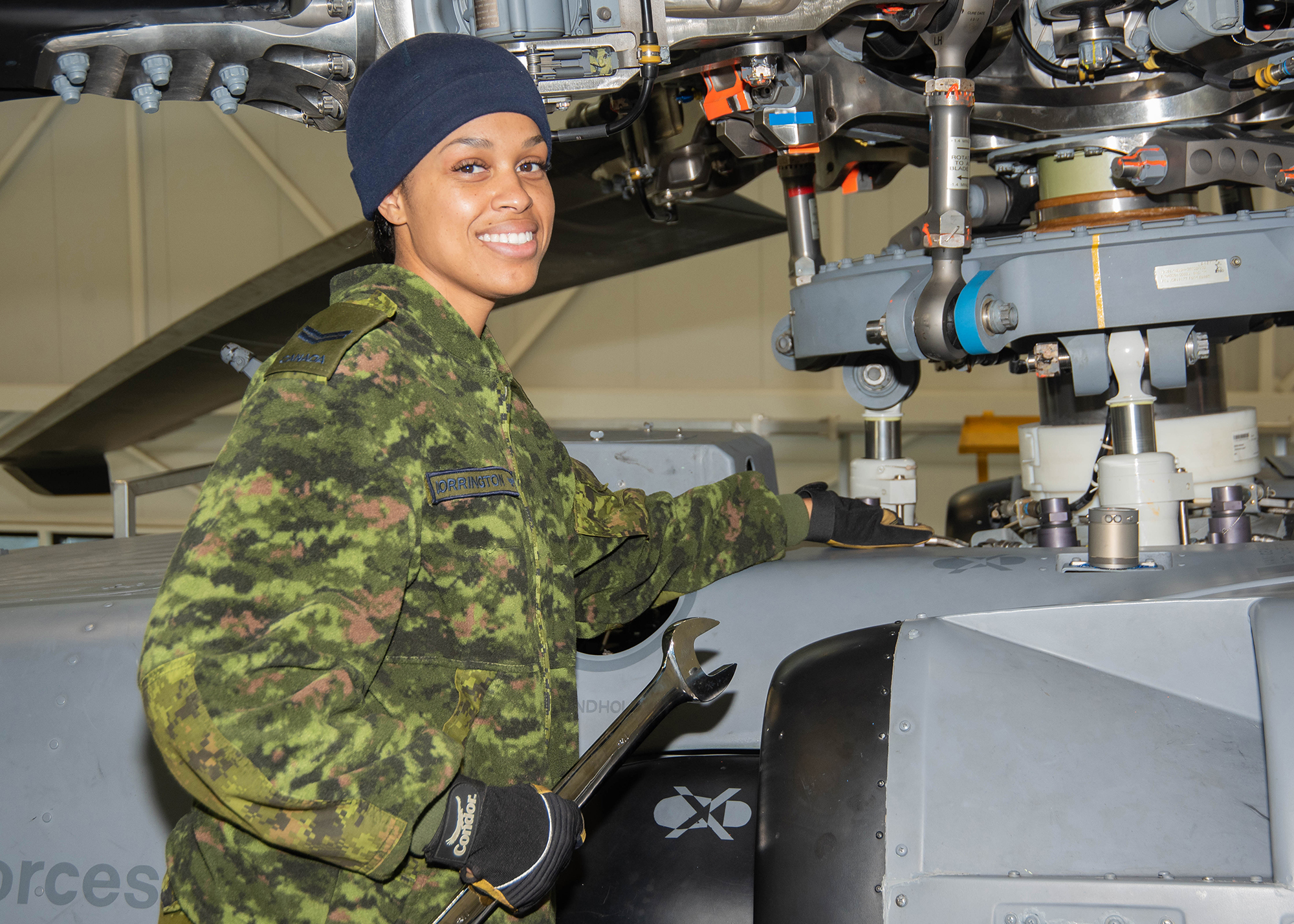 A woman wearing a disruptive pattern uniform, and gloves and a cap, works on the rotor mechanism of a helicopter.