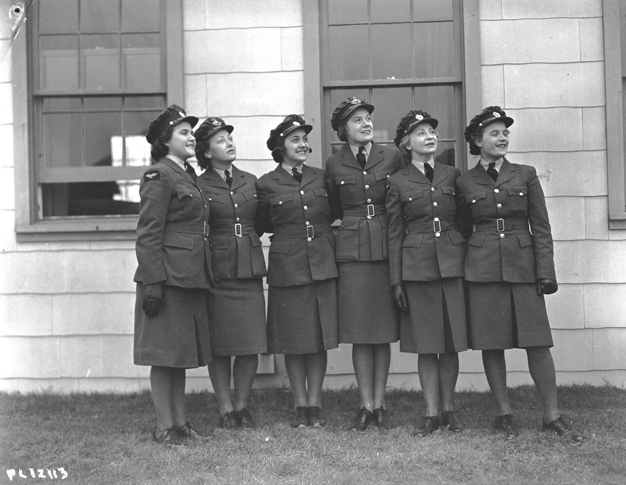 A black-and-white photo of six uniformed women standing in a row with their arms around each other's waists, looking up.
