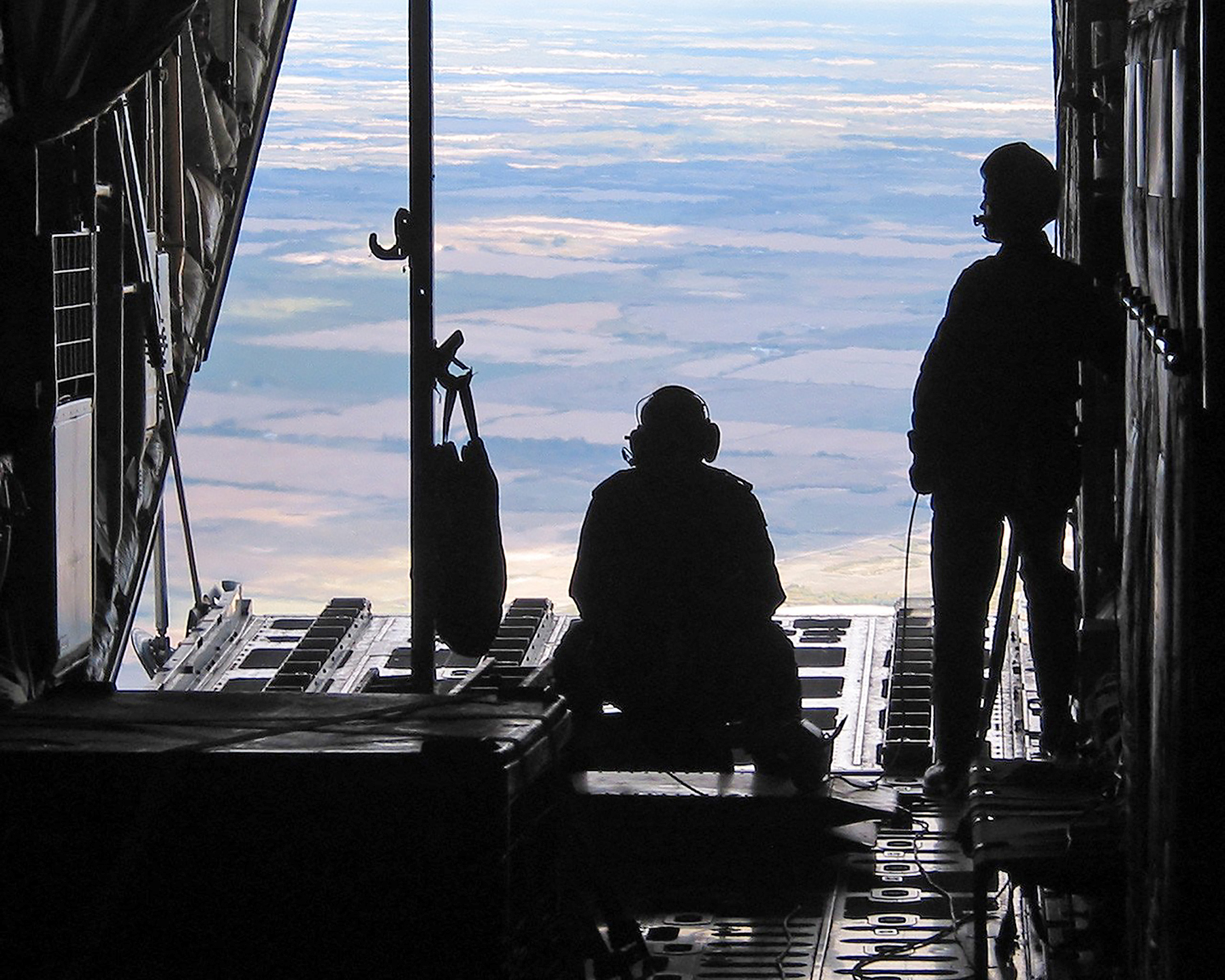 During a CC-130H Hercules test flight in Abbotsford, British Columbia, in 2003, Master Warrant Officer Laurie Moore (standing) observes the amount of time it takes for the cargo door and ramp to open and then close, to ensure that both actions take place within the allowable time limits, while a flight engineer serves as the safety person. PHOTO: DND