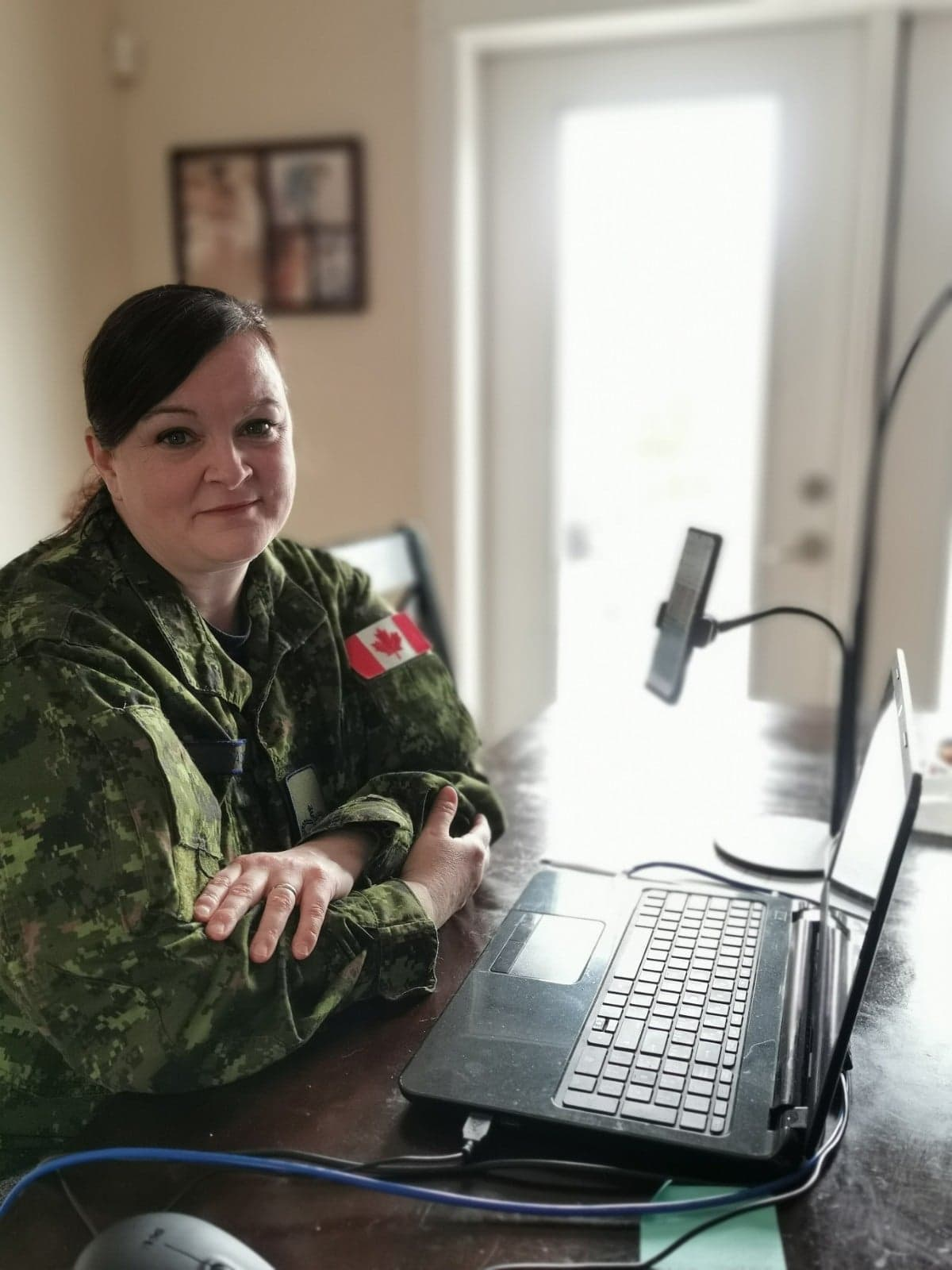 A woman wearing a disruptive pattern uniform sits at a desk with a laptop.