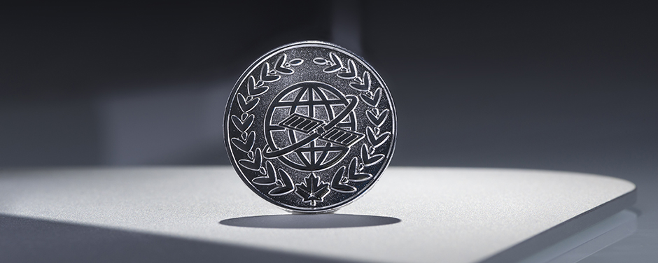 slide - A circular silver metal badge with a globe, a laurel wreath and maple leaf.
