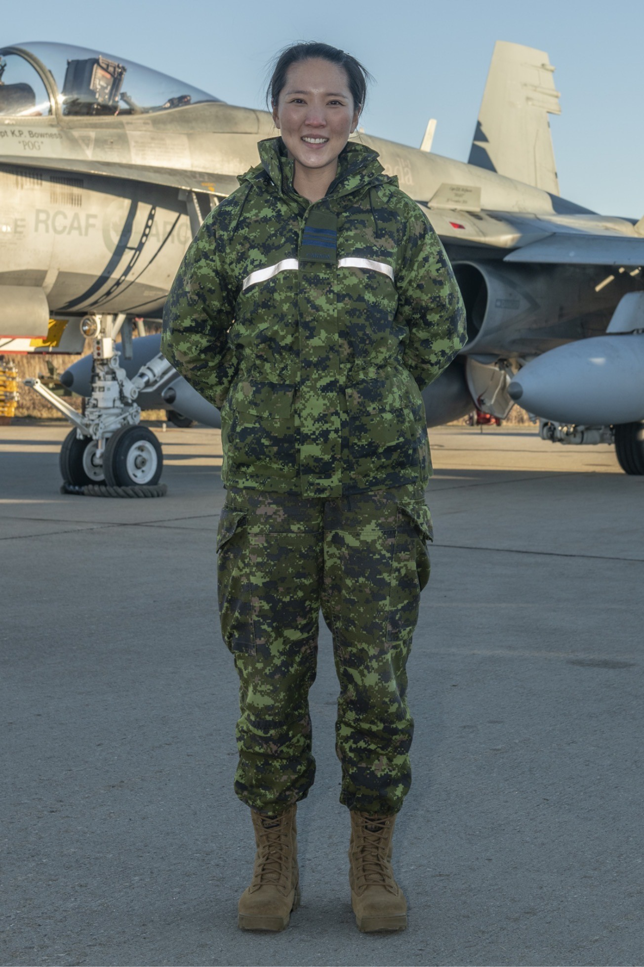 A smiling woman wearing a disruptive pattern uniform stands in front of a jet fighter.