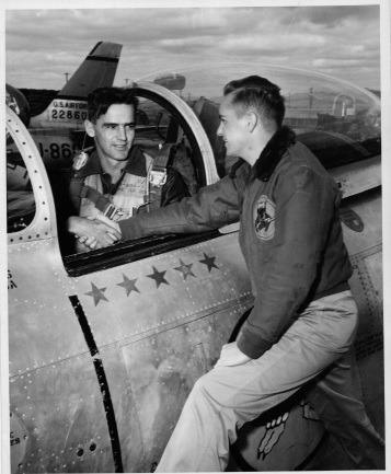 A vintage photo of two men shaking hands, one sitting in the cockpit of an aircraft and the other standing beside it.