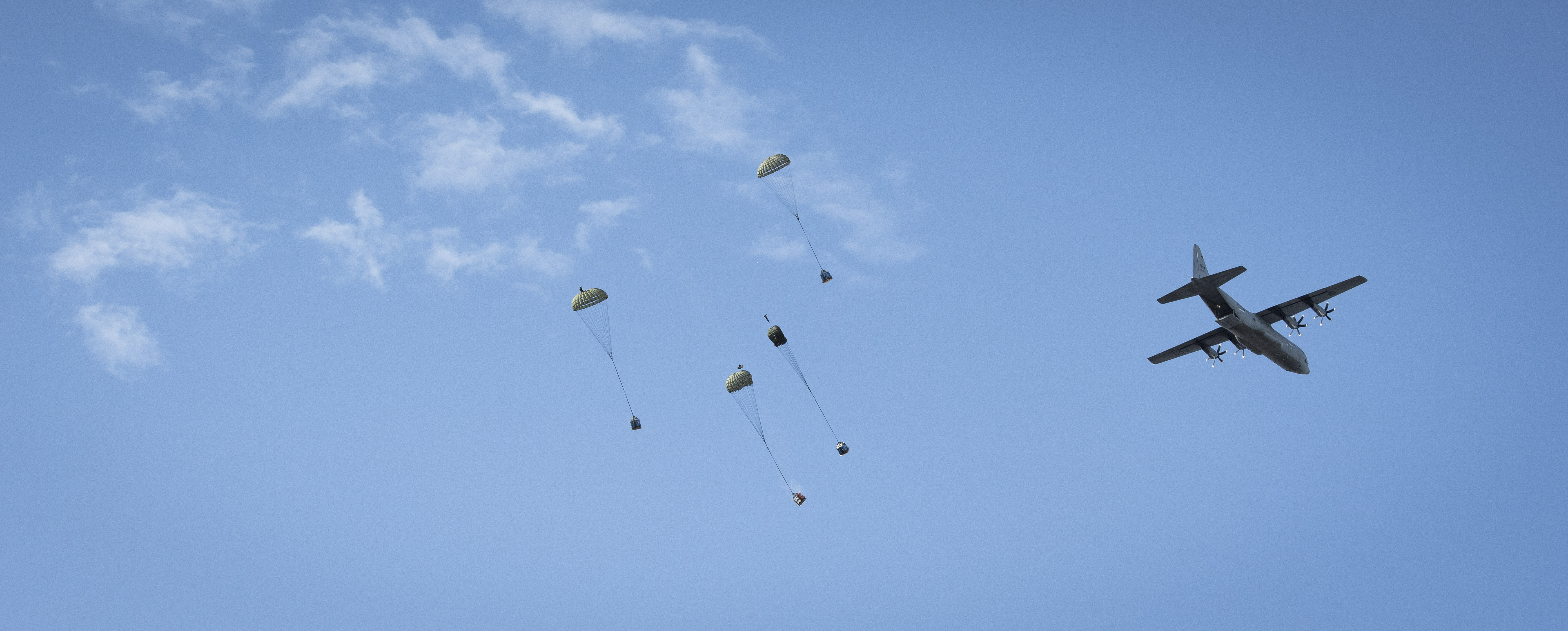 Four containers attached to parachutes falling in the sky with a large grey propeller aircraft flying overhead on the right.