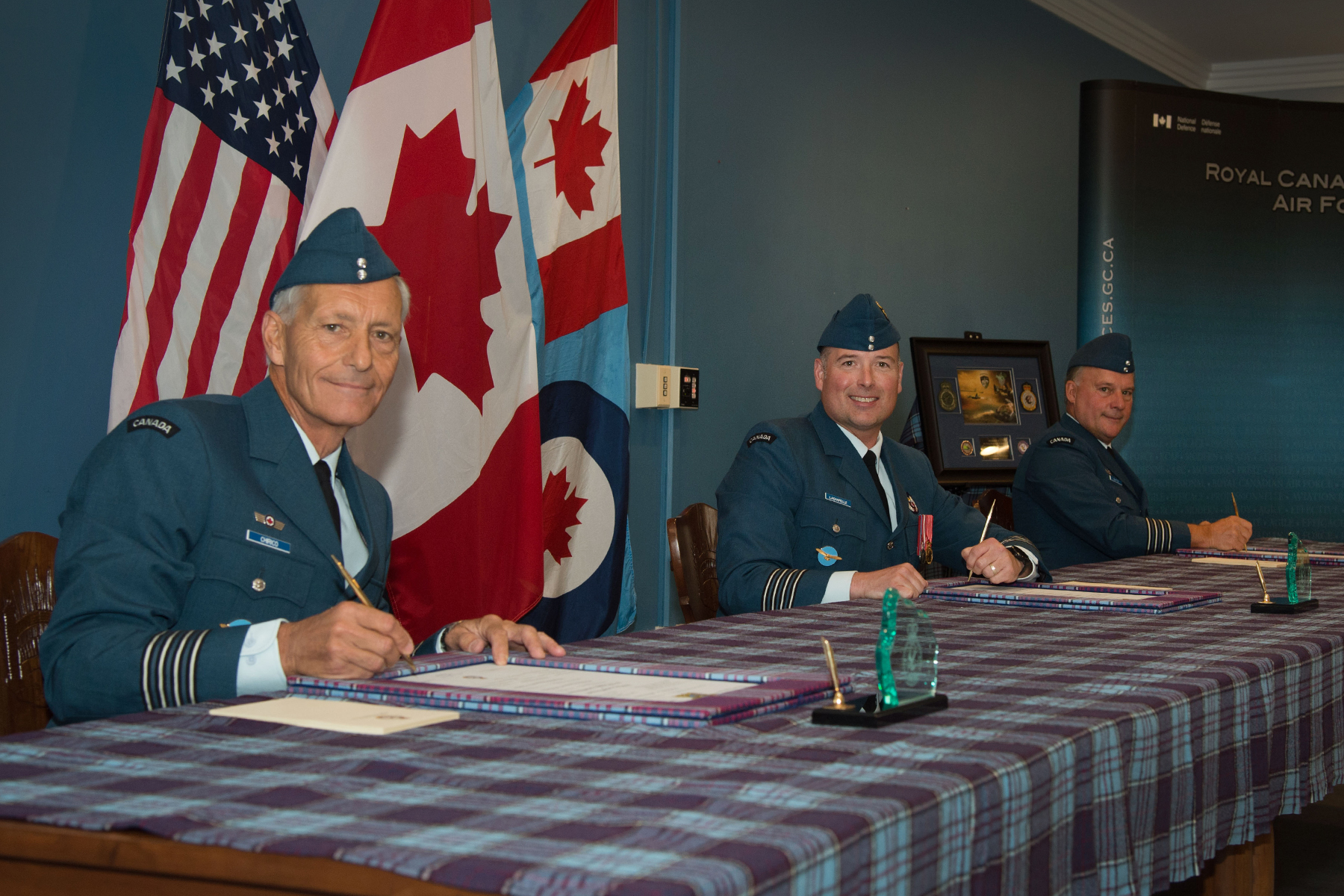 Three men wearing blue military uniforms and holding pens sit at a table covered with a tartan cloth on which there are documents. Behind the men are three flags.