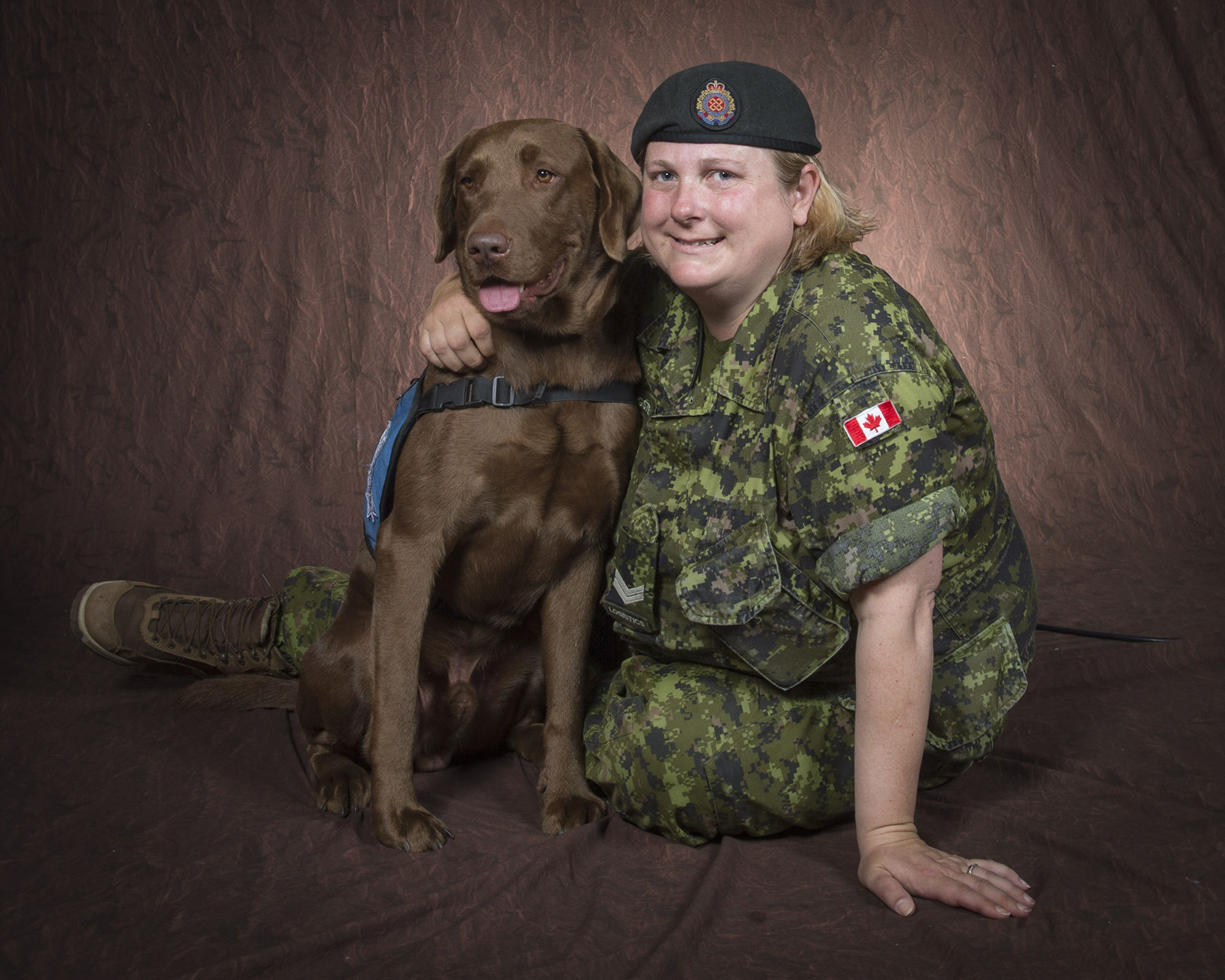 A woman wearing a military disruptive pattern uniform sits beside a chocolate-coloured Labrador dog. She has her right arm wrapped around the animal.