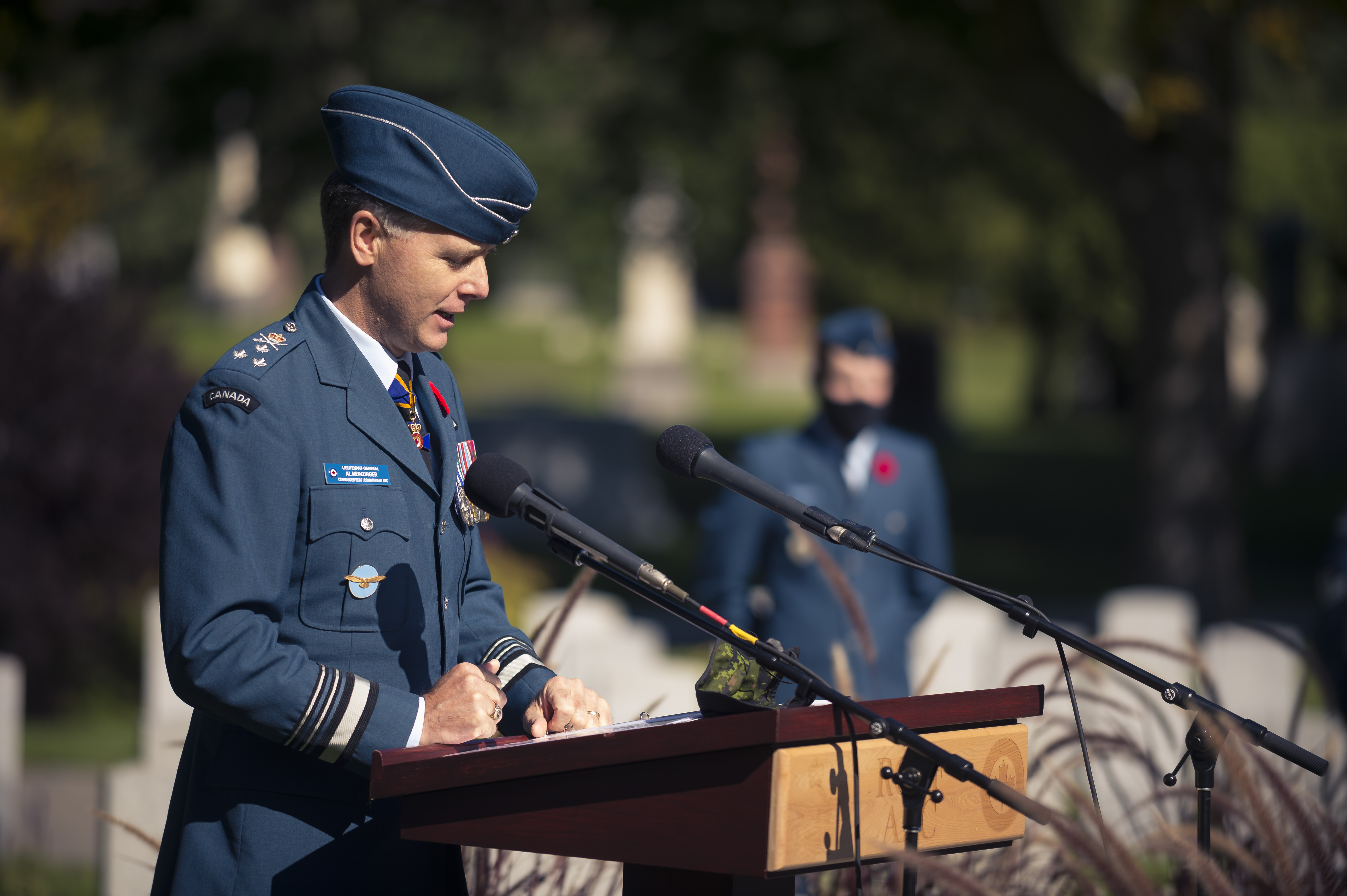 A man wearing a blue military uniform and wedge hat speaks behind a podium and microphones.