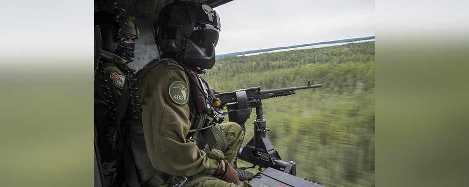 slide - Two men wearing green flight suits and black helmets, one of which mans a machine gun, sit at the open door of a helicopter flying over a wooded area.