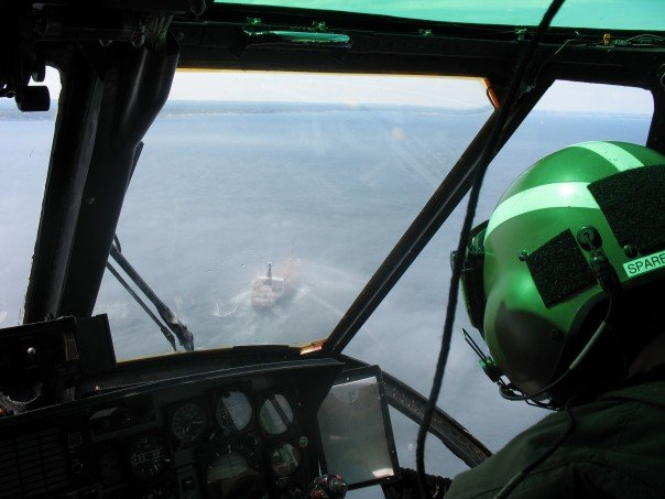 A photo taken from the cockpit of a helicopter flying over water. Through the aircraft windshield, a ship can be seen. On the right, in the helicopter, is a man wearing a flight helmet.