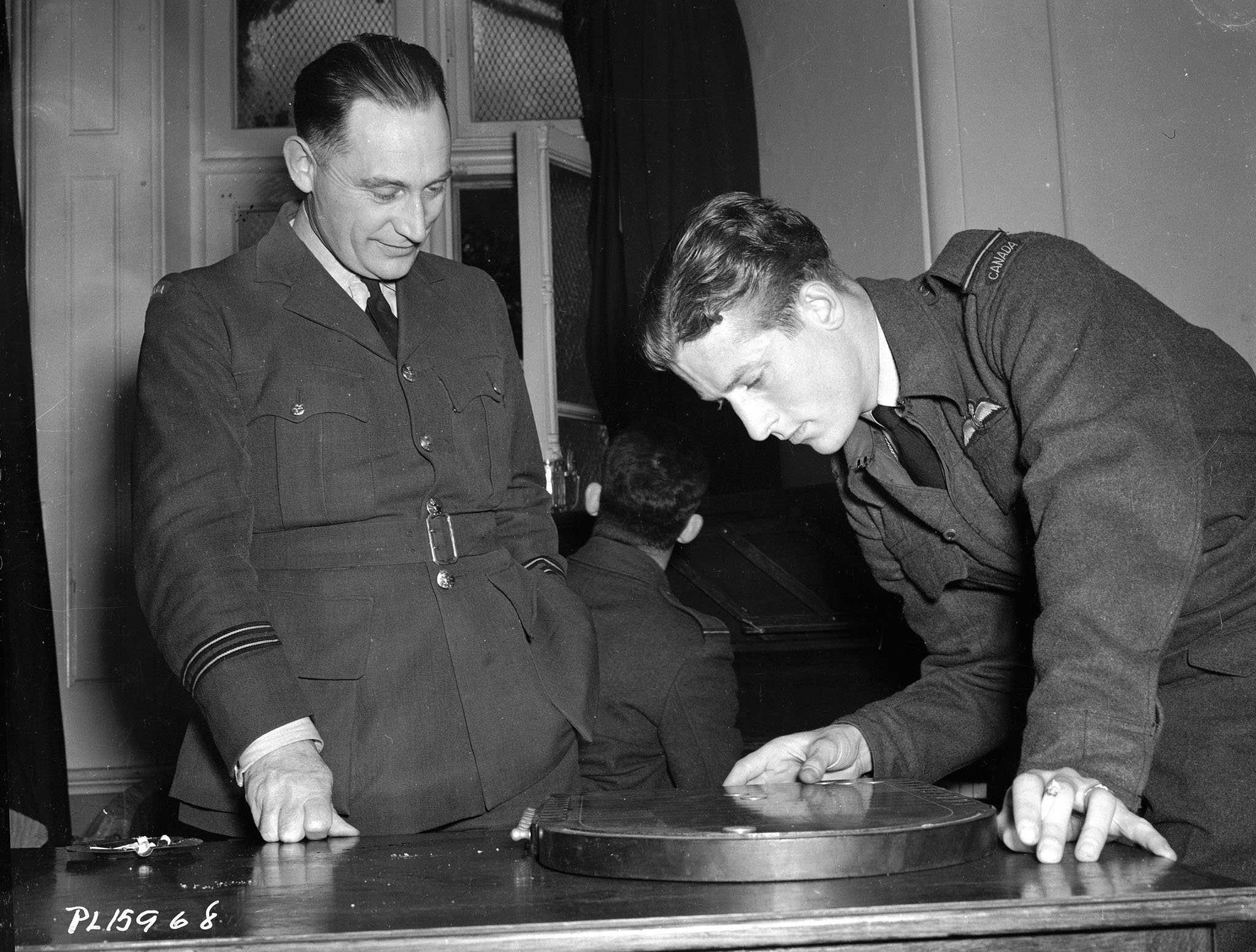Two men wearing military uniforms look at a flat round object on a table.