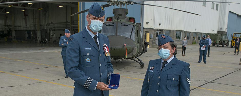 slide - A man and a woman wearing blue military uniforms stand in front of a hangar and a helicopter. The man presents the woman with a medal in a little blue case.