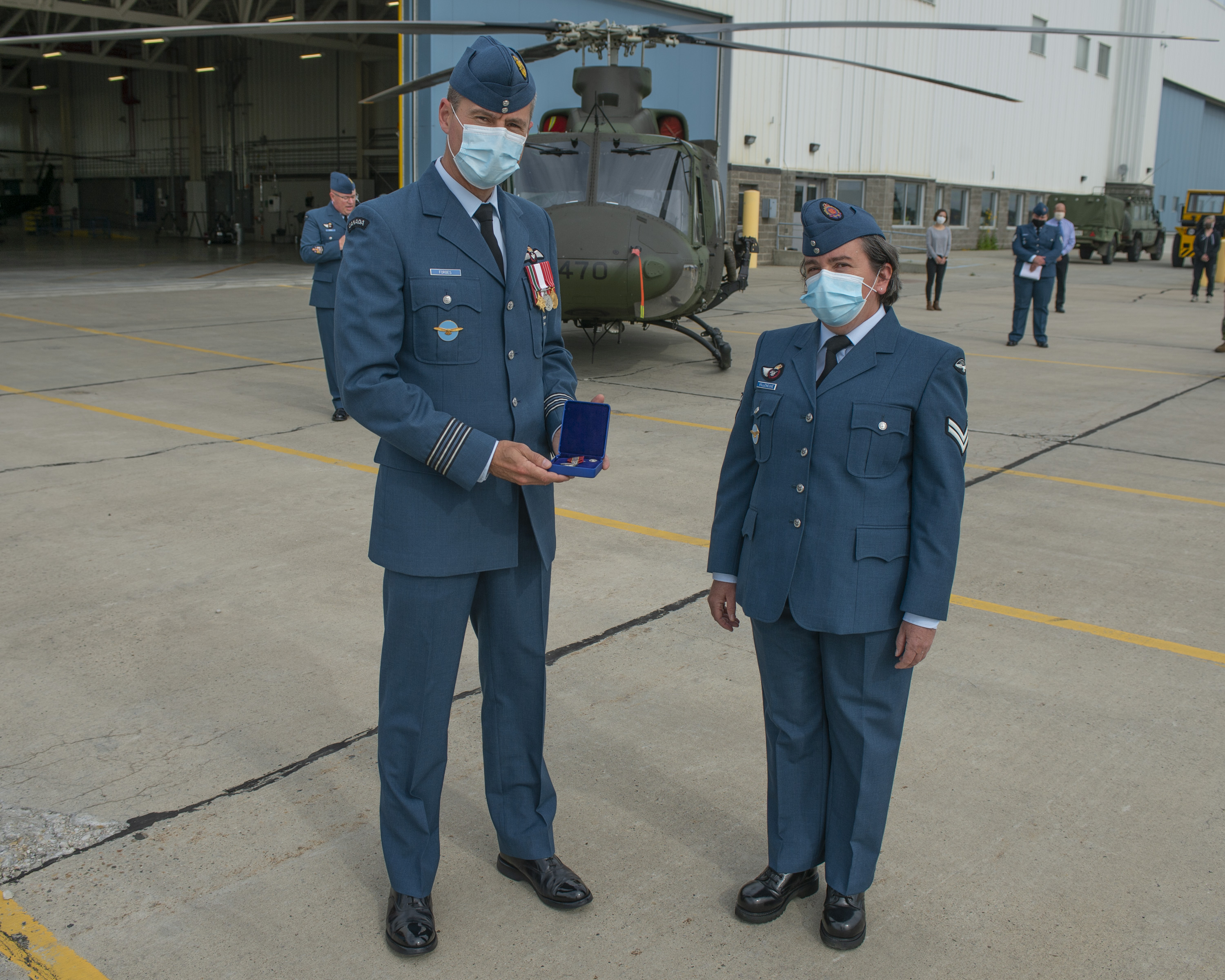 A man and a woman wearing blue military uniforms stand in front of a hangar and a helicopter. The man presents the woman with a medal in a little blue case.