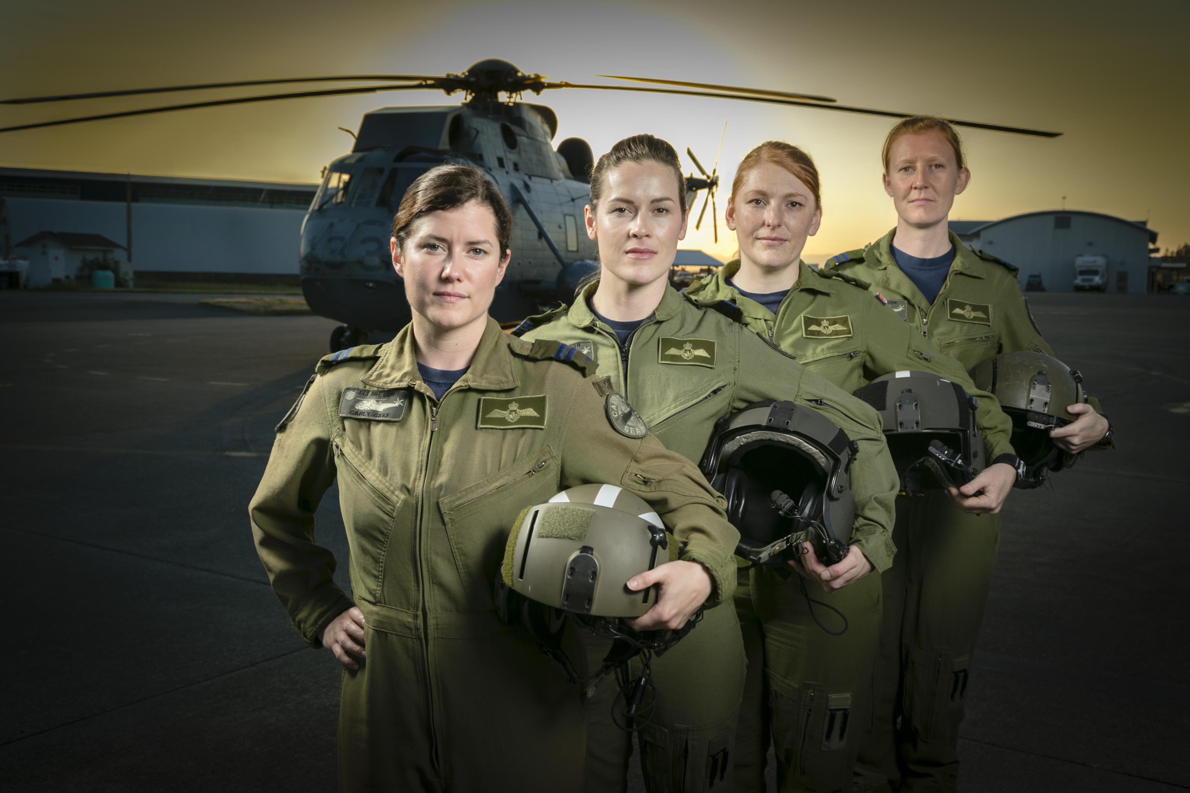 Four women wearing green flight suits and holding a helmet stand in front of a helicopter.