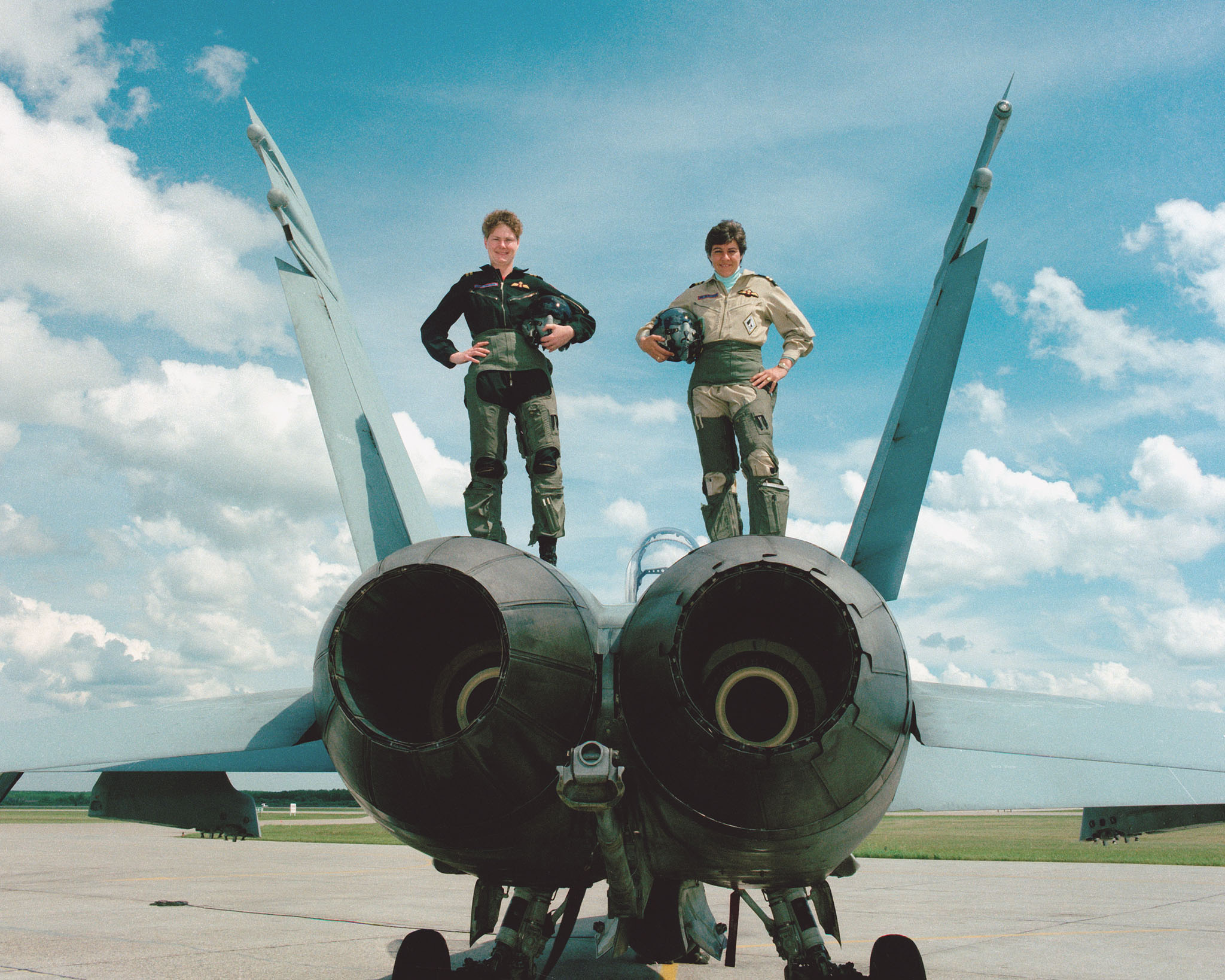 "On June 20, 1989, Captain Jane Foster (left) and Captain Deanna ""Dee"" Brasseur stand atop a CF-188 Hornet fighter jet. According to the original caption of this photo, they were at that time the only two women in the world flying fighter jets in operational squadrons. In 1979, Captain Brasseur, Captain Leah Mosher and Captain Nora Bottomley had become the first women in the Canadian Armed Forces to earn their pilots' wings after the occupation opened to women. PHOTO: CKC89-3773, DND Archives"