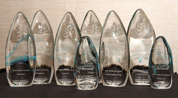 Eight glass awards on a table.