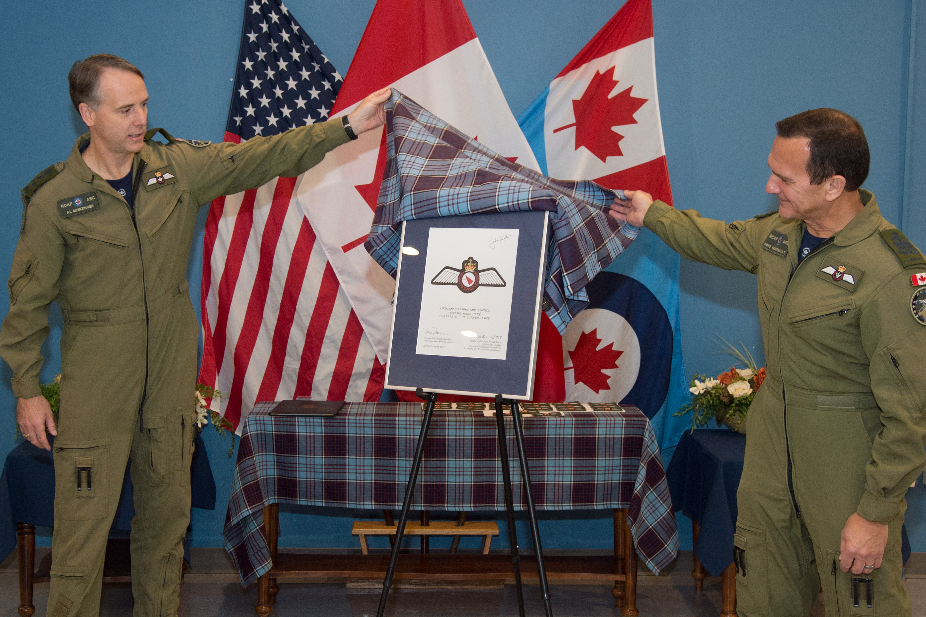 Two men in green flight suits unveil a badge on a stand. Behind them are three flags.