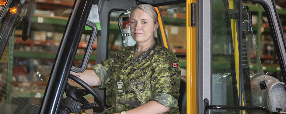 slide - A woman wearing a camouflage uniform sits at the wheel of a vehicle.