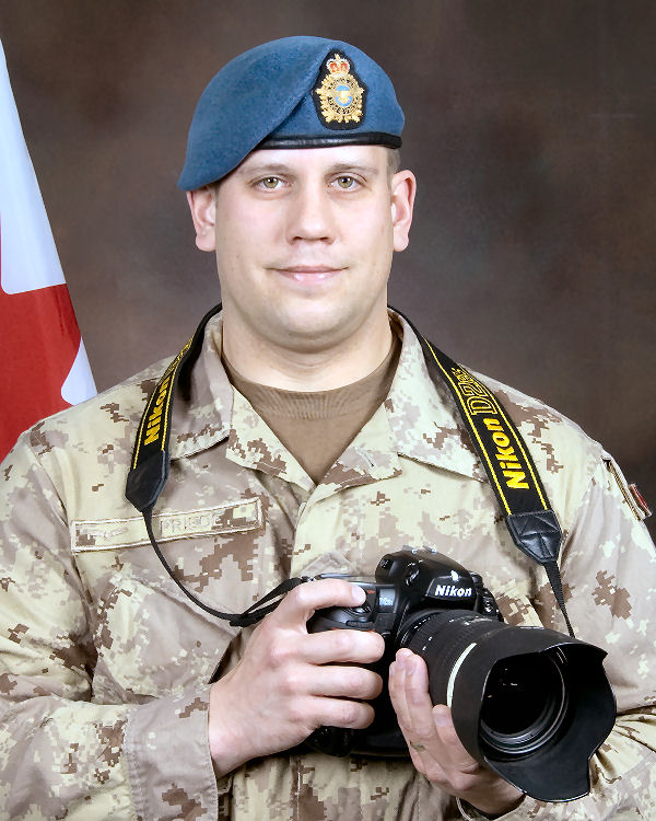 A man wearing a tan camouflage uniform and blue beret holding a camera.