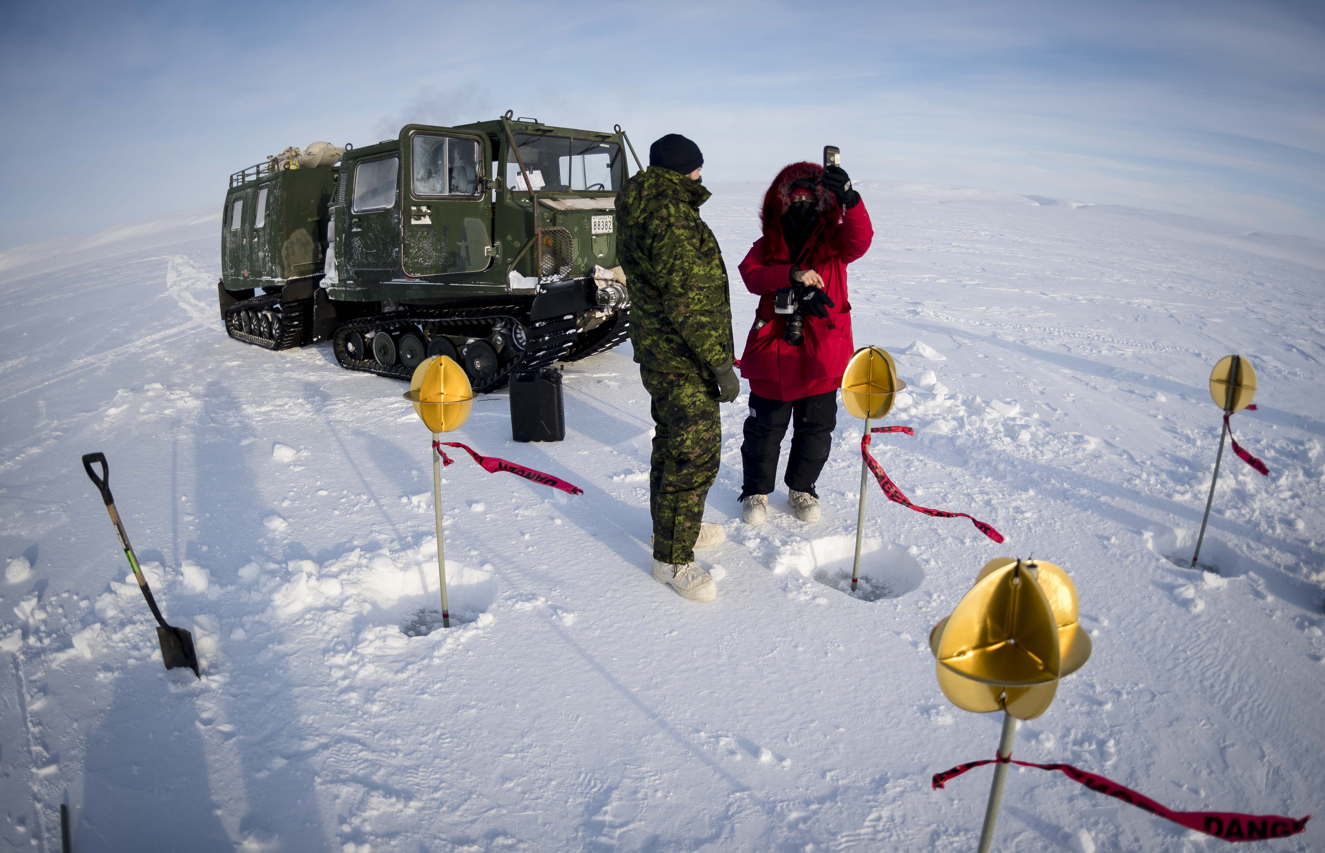 Two people, one wearing a camouflage uniform and the other winter clothing, stand in snow in front of a green tracked vehicle. Around them are small poles planted in the snow with round yellow objects at their tip.