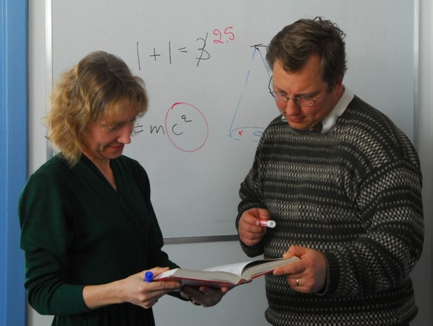 A woman and a man wearing civilian clothes look at an open book that they are both holding. Behind them is a white board on which are scribbled mathematical equations.
