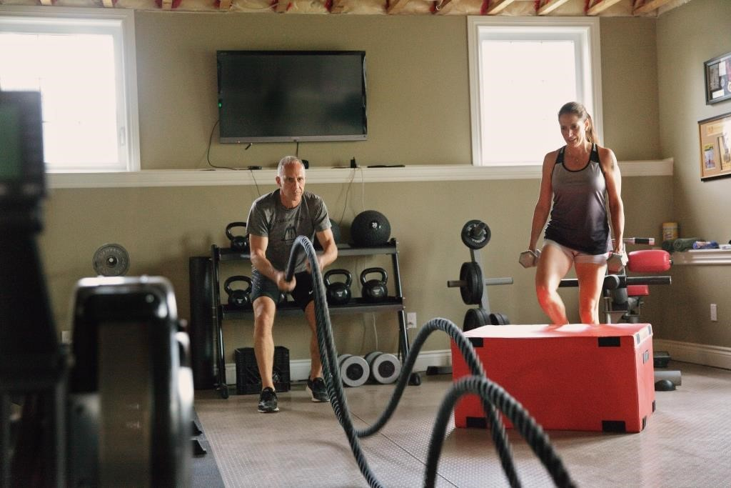 A man and a woman work out in a home gym.