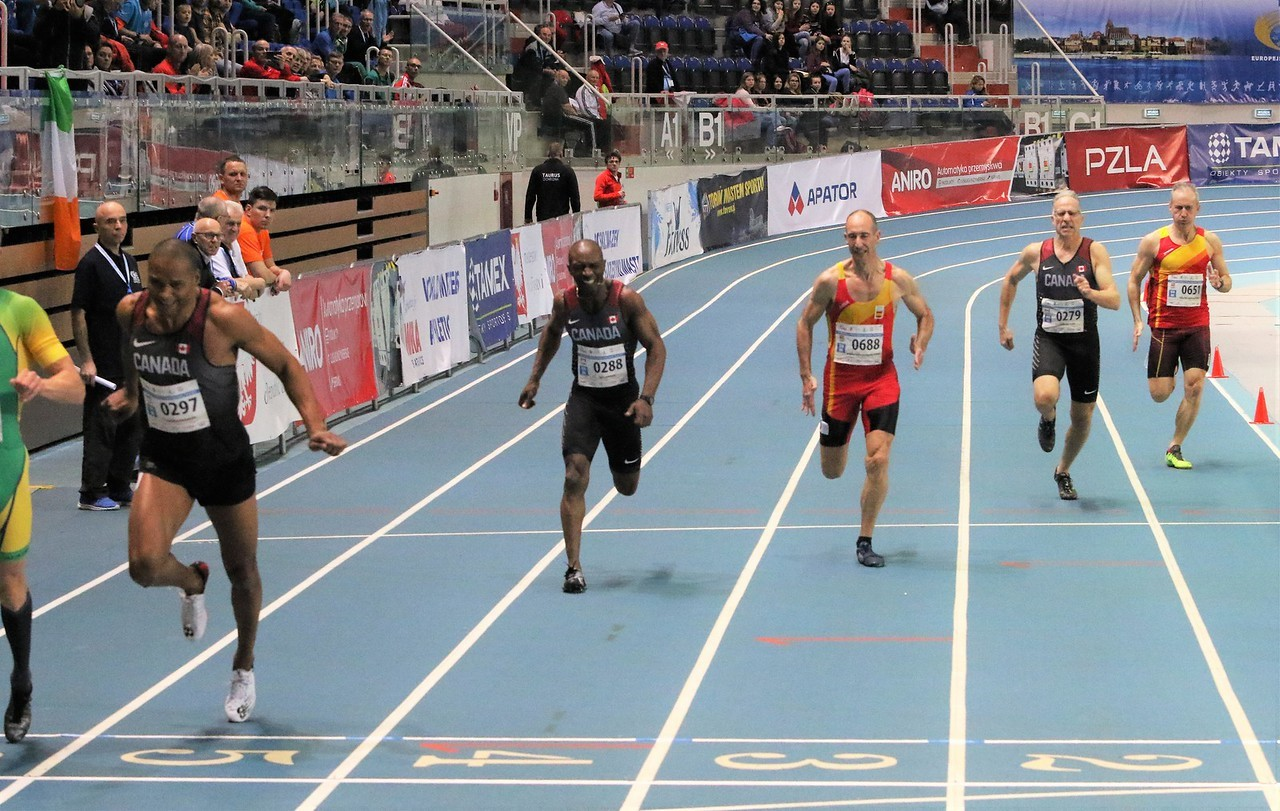 Six men run on a track in a stadium.