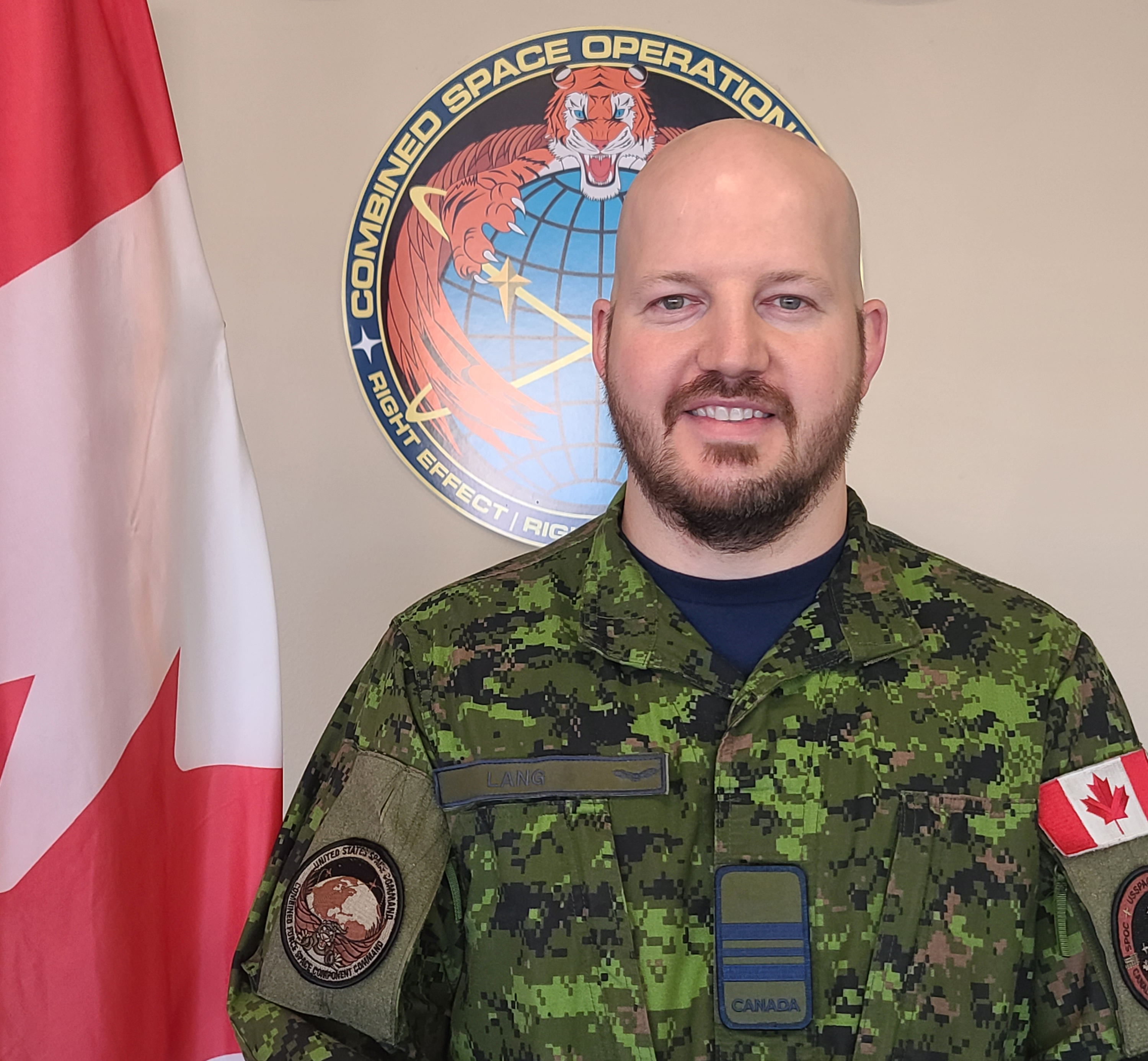 A man wearing a military camouflage uniform stands in front of a Canadian flag and military crests.