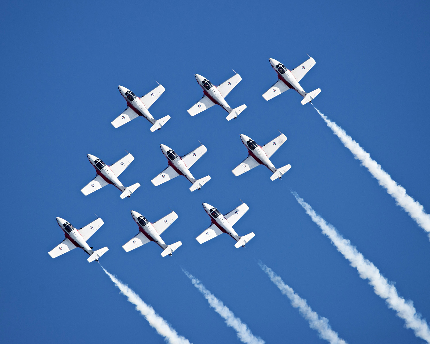 Nine jet aircraft fly in tight formation in a blue sky.