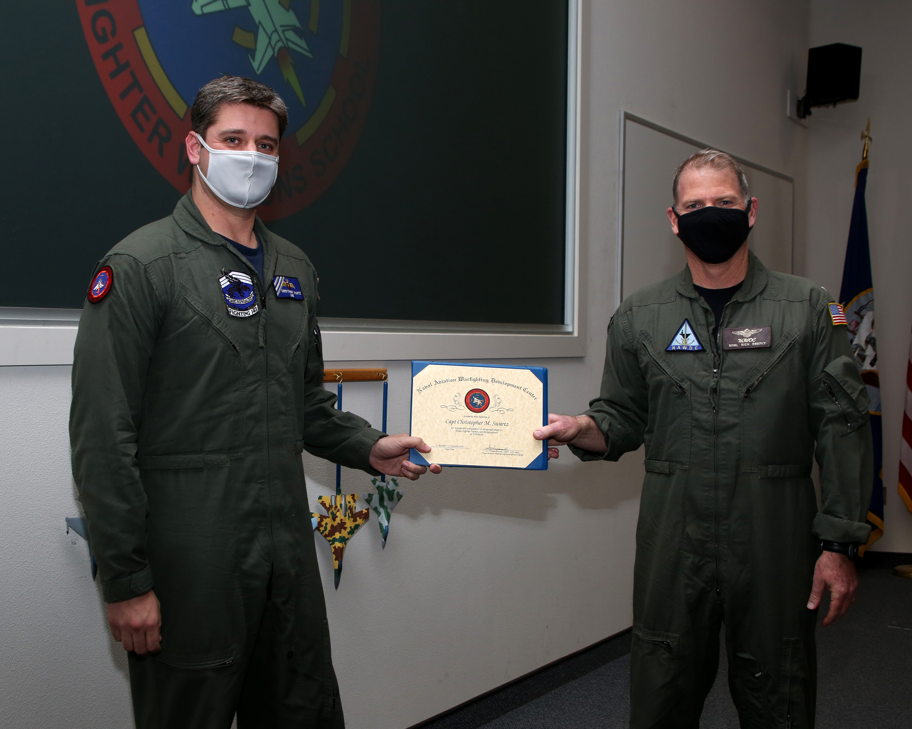 Two men wearing green flight suits and masks hold a certificate together.